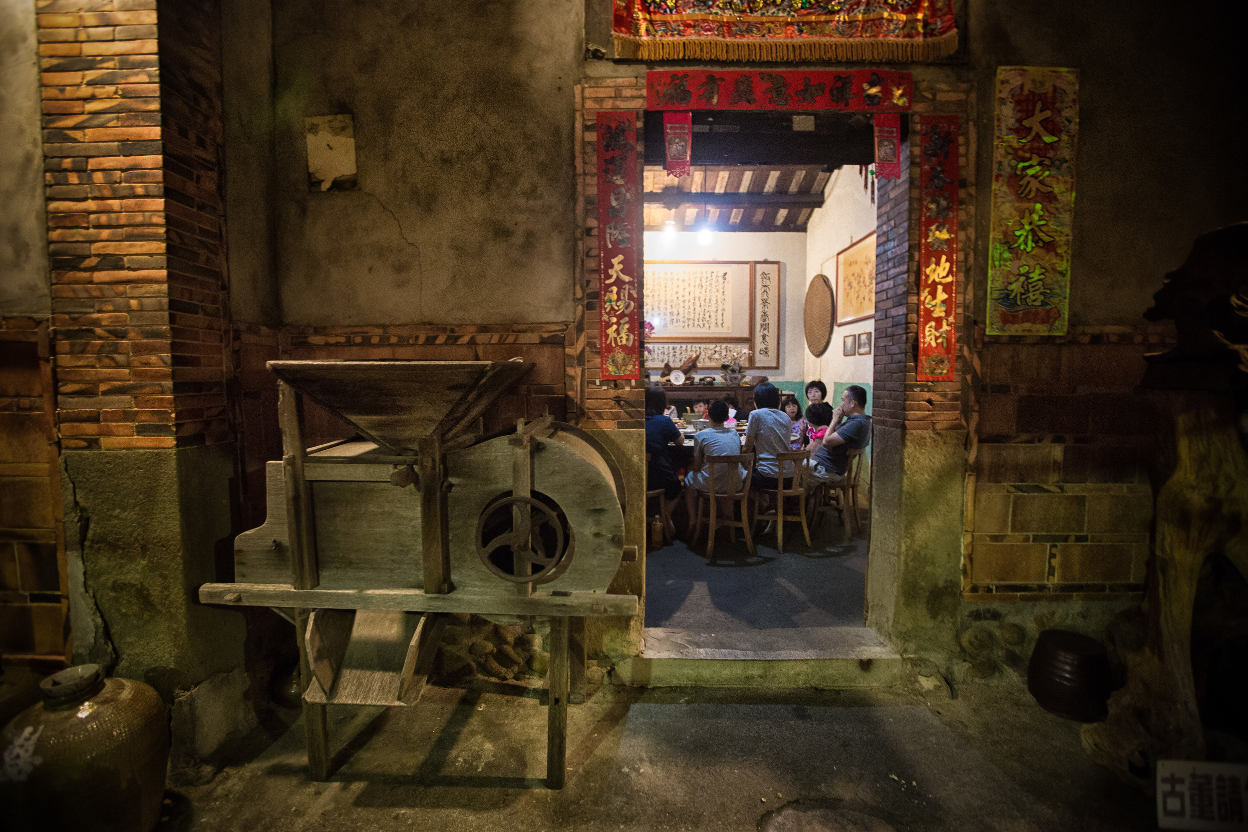 A large family having dinner in the main dining room with a rice tiller outside.