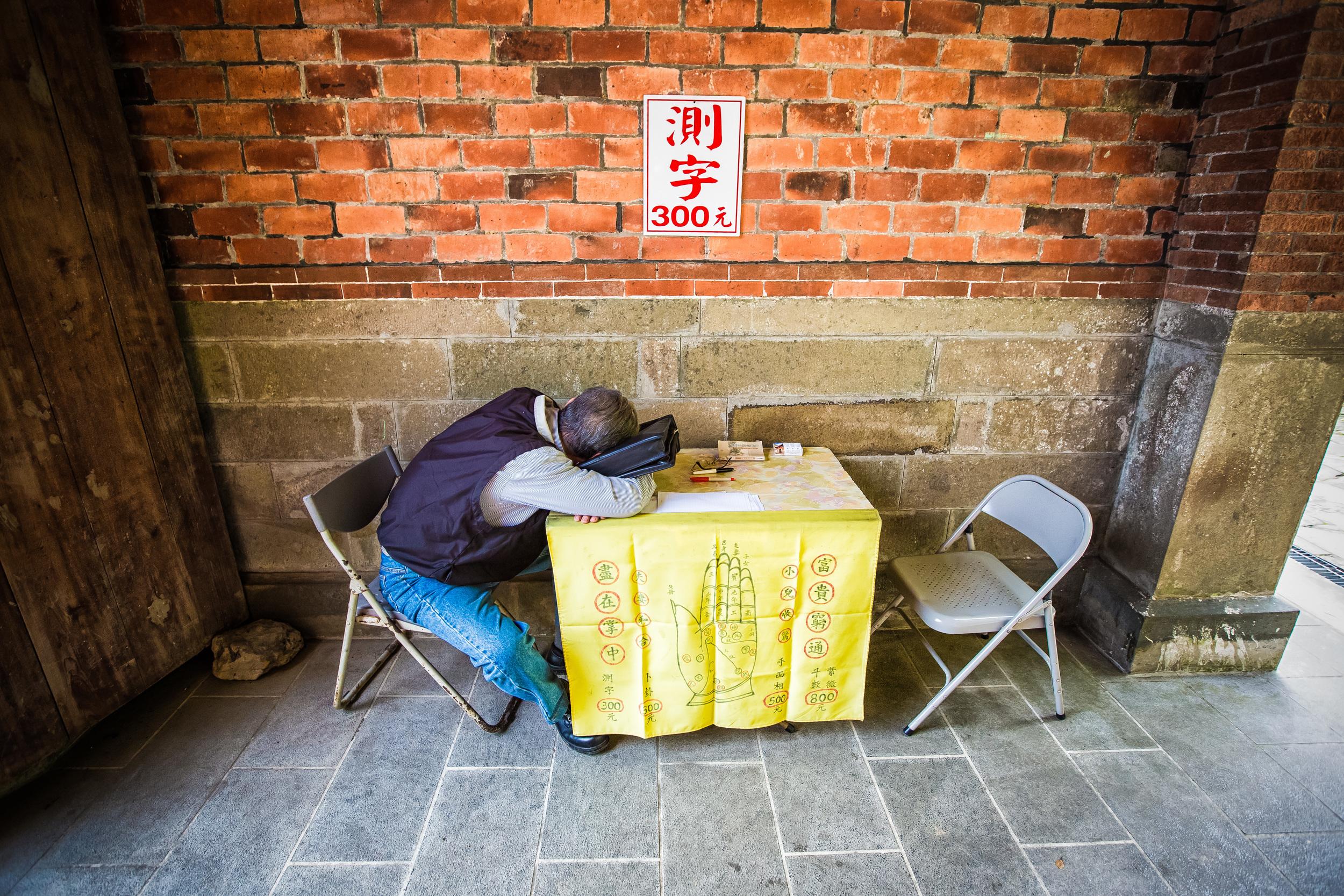 A fortune teller taking a break at Fu Tian Temple