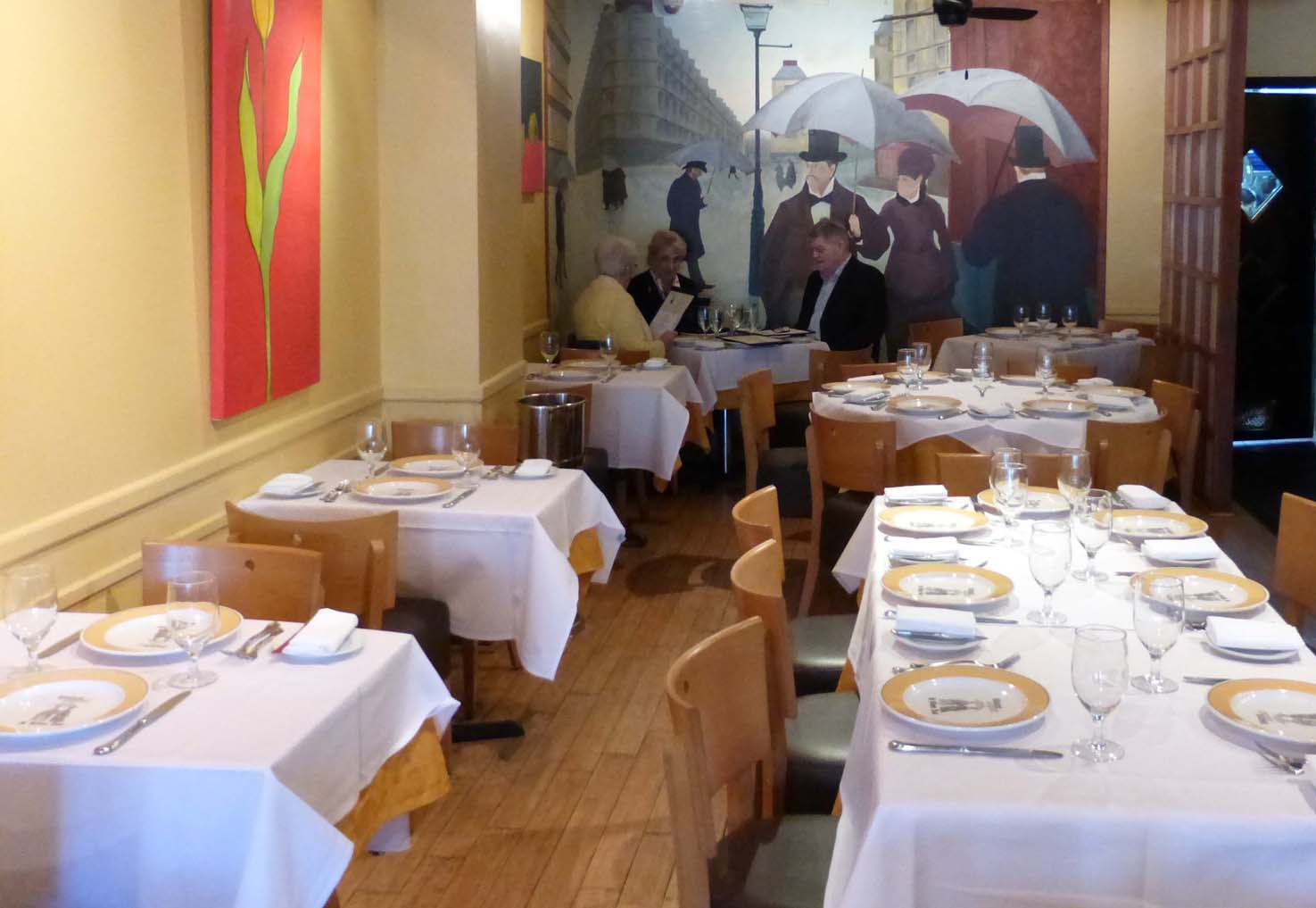 seated by a mural of Caillebotte 's  1877 rainy paris street scene, patrons enjoy an early lunch. photos by ann carper.