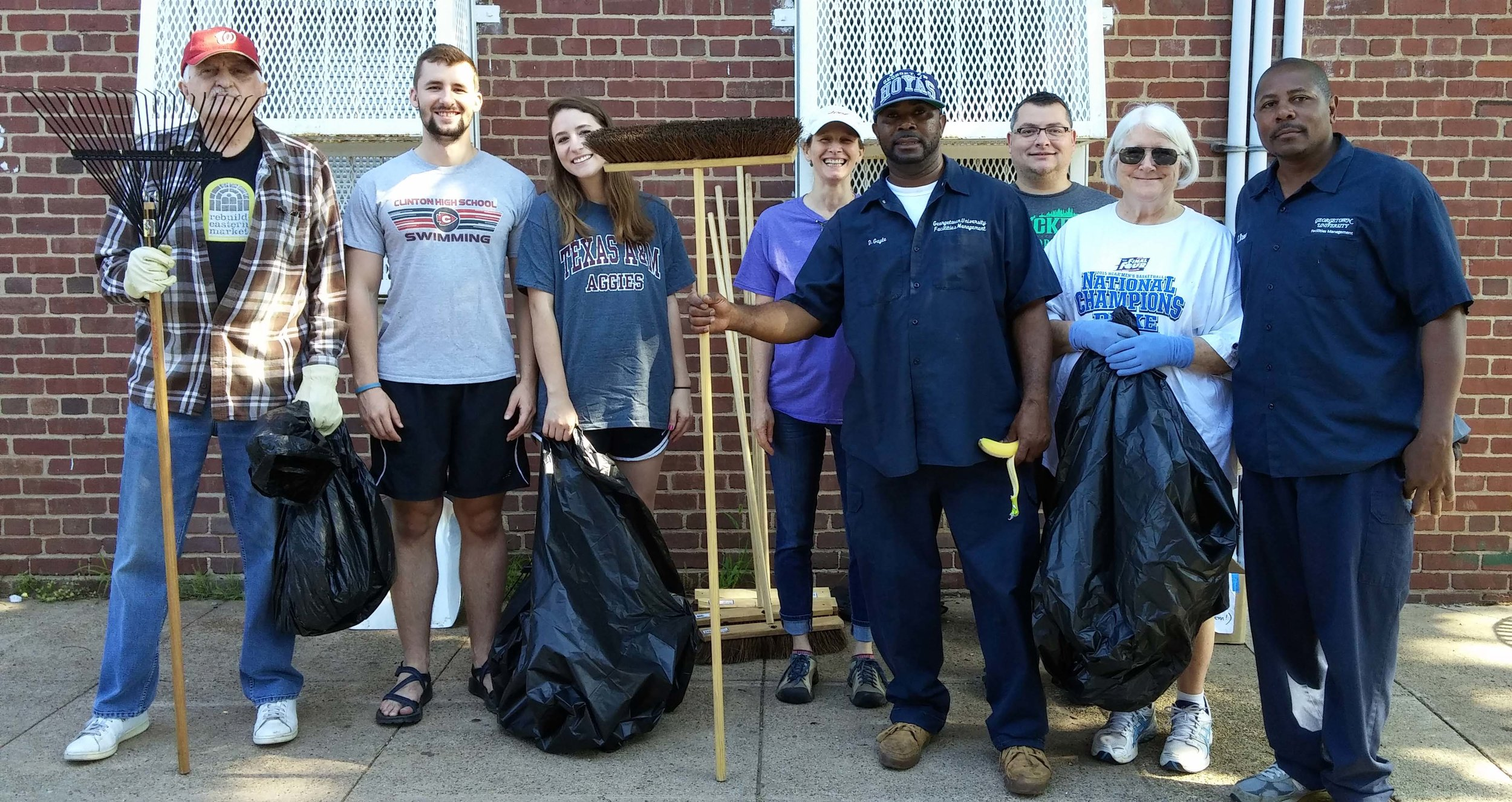 Armed with rakes, brooms, and garbage bags, GU staff and neighbors prepare to go to work.