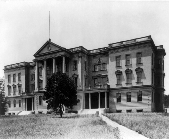 """This image dates to around 1900, two years after the Western High School building was built. It shows the newly planted trees along with a """"Keep off the Grass"""" warning to protect the new lawn."""