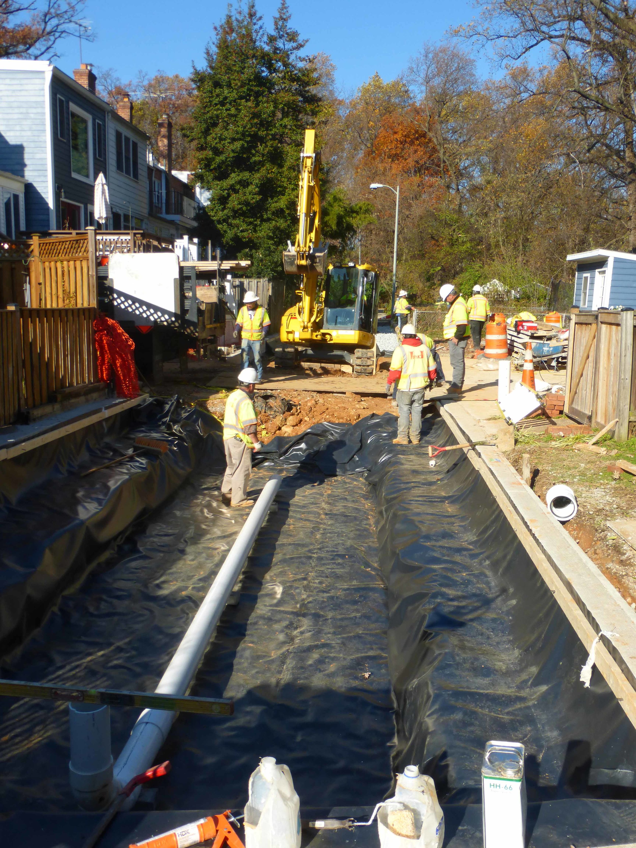 Sheets of waterproofing line the excavated alley to collect run off. Water travels through a perforated PVC pipe connected to the sewer system where it is slowly released back into the system after the rain storm has ended.