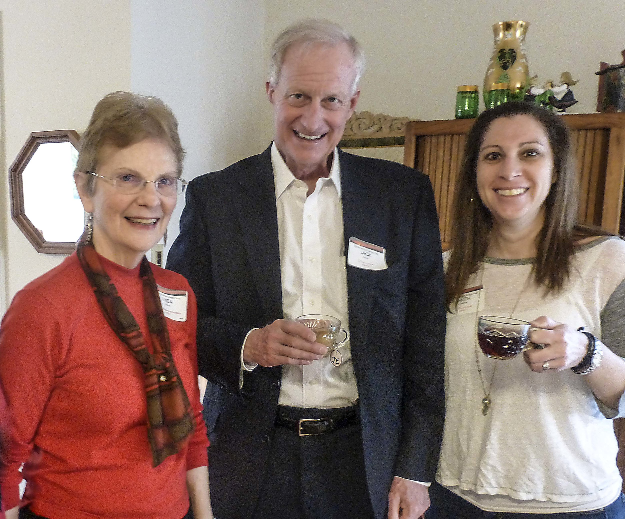 Jack Evans and Ruth Werner share a cup of cheer with host Linda Brooks. Photo by Ann Carper.