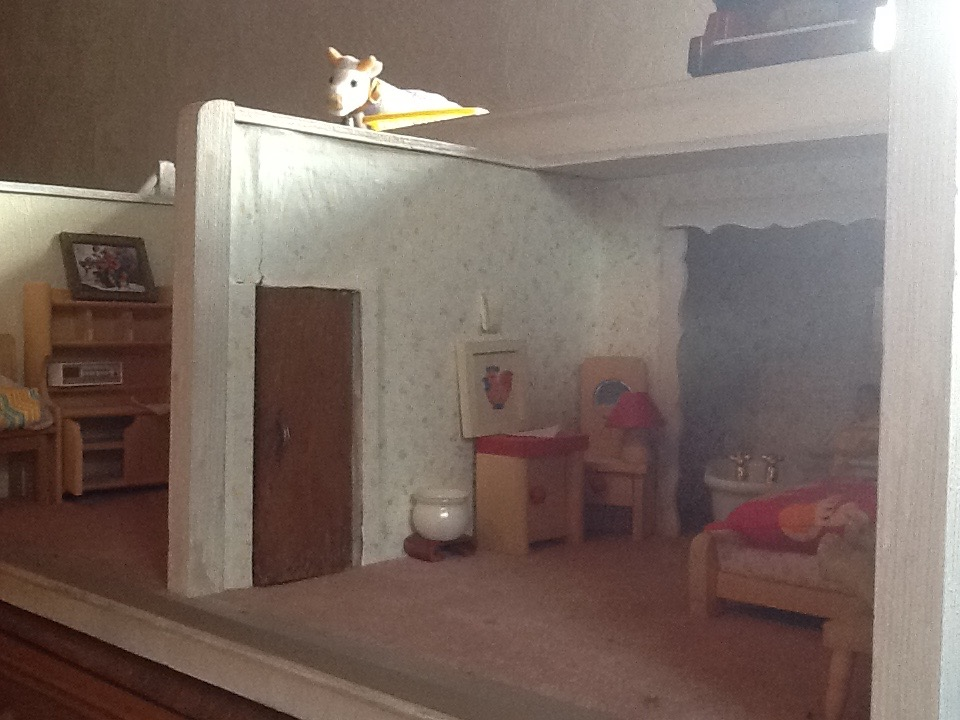Dollhouse view showing sentinel cow (and a glimpse of the piano).