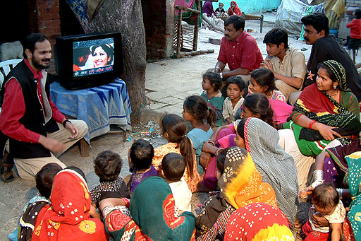 people watching television together. Talking to them is Brij Kothari, who increased literacy by inventing same-language subtitles on TV.  Wikimedia  pic.