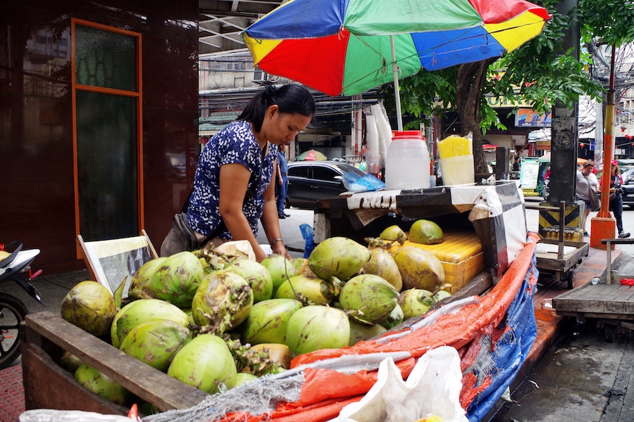 A mother selling drinking coconuts in Manila. Photo by  Alee Catagatan.