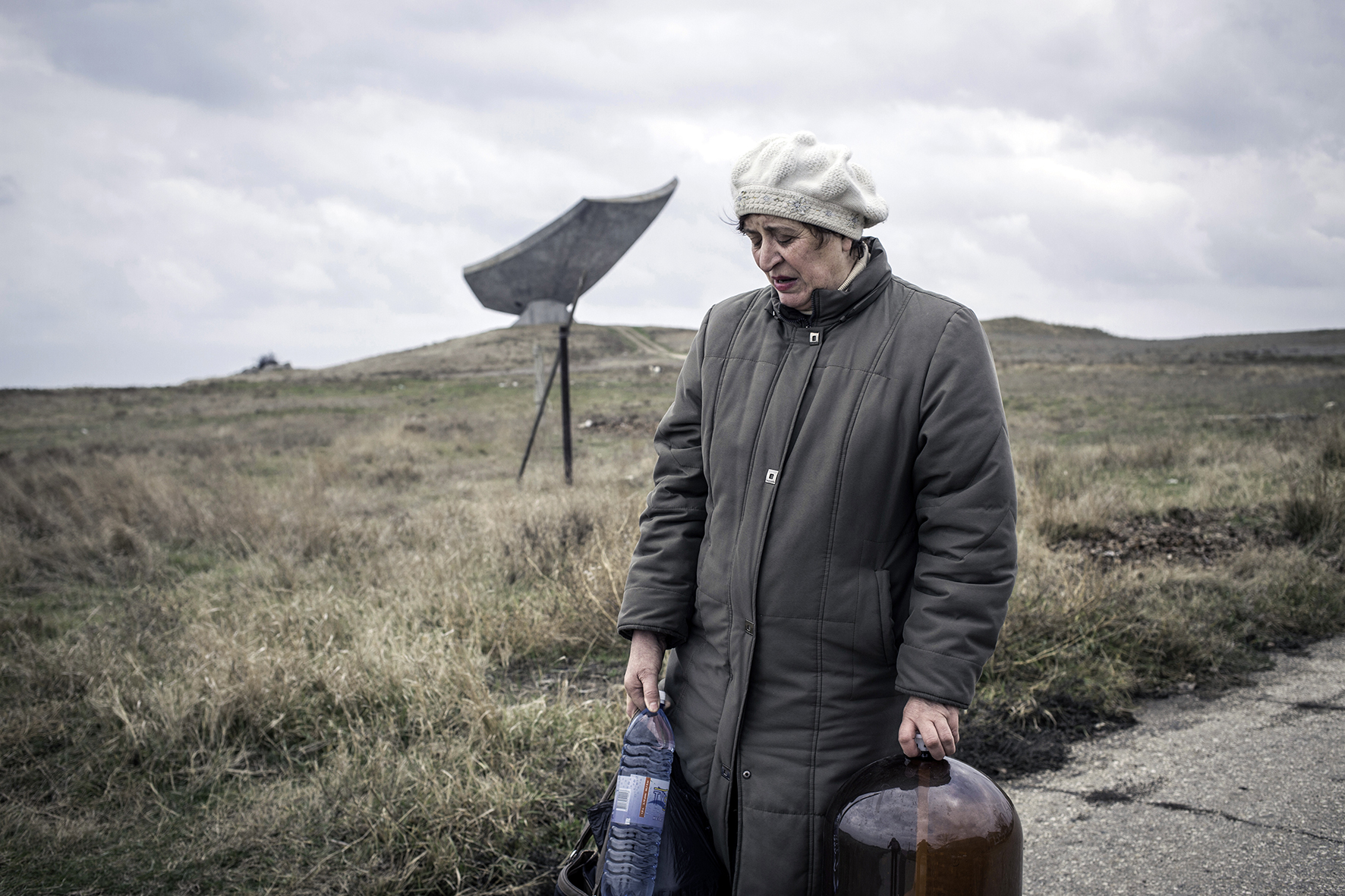 Woman in a village near Kerch, carrying home canisters with drinking water, Crimea, 2014