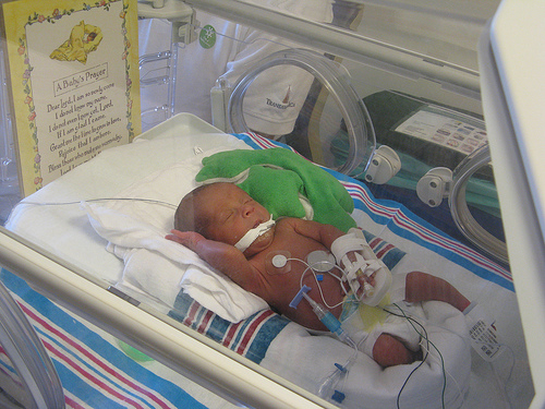 preemie in incubator with IV in hand, oral feeding tube