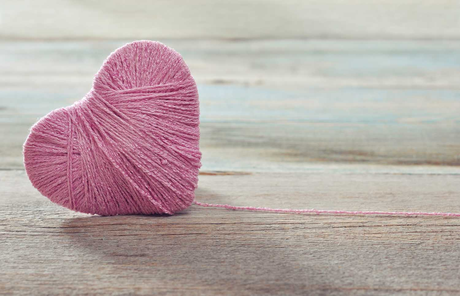 pink heart for a NICU baby, wrapped in pink string on wooden table