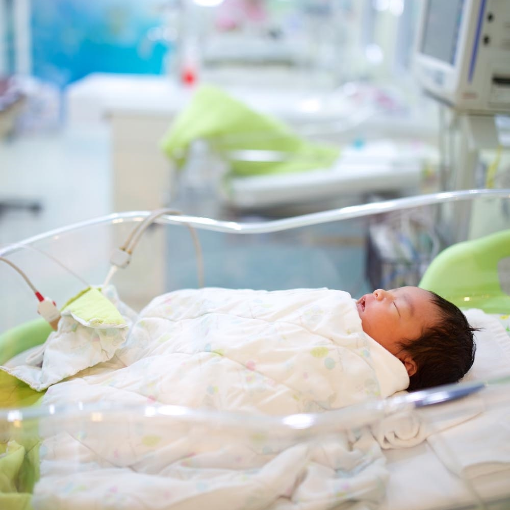 asian preemie baby laying supine in NICU bed
