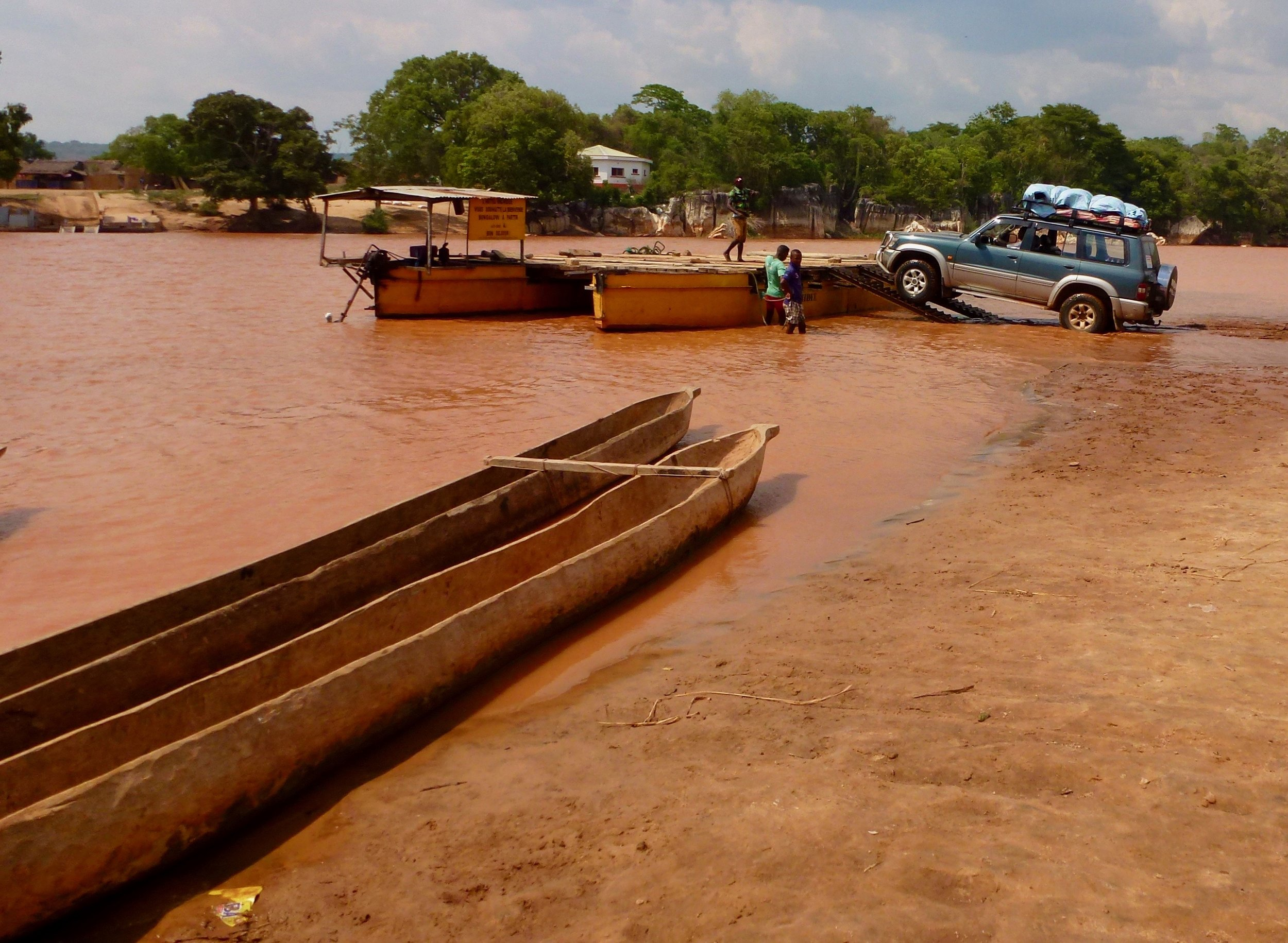 Our jeep was loaded onto a ferry to cross the river, as there are no bridges. Notice the red river. It's colored by the soil that has washed down from where forests once stood.
