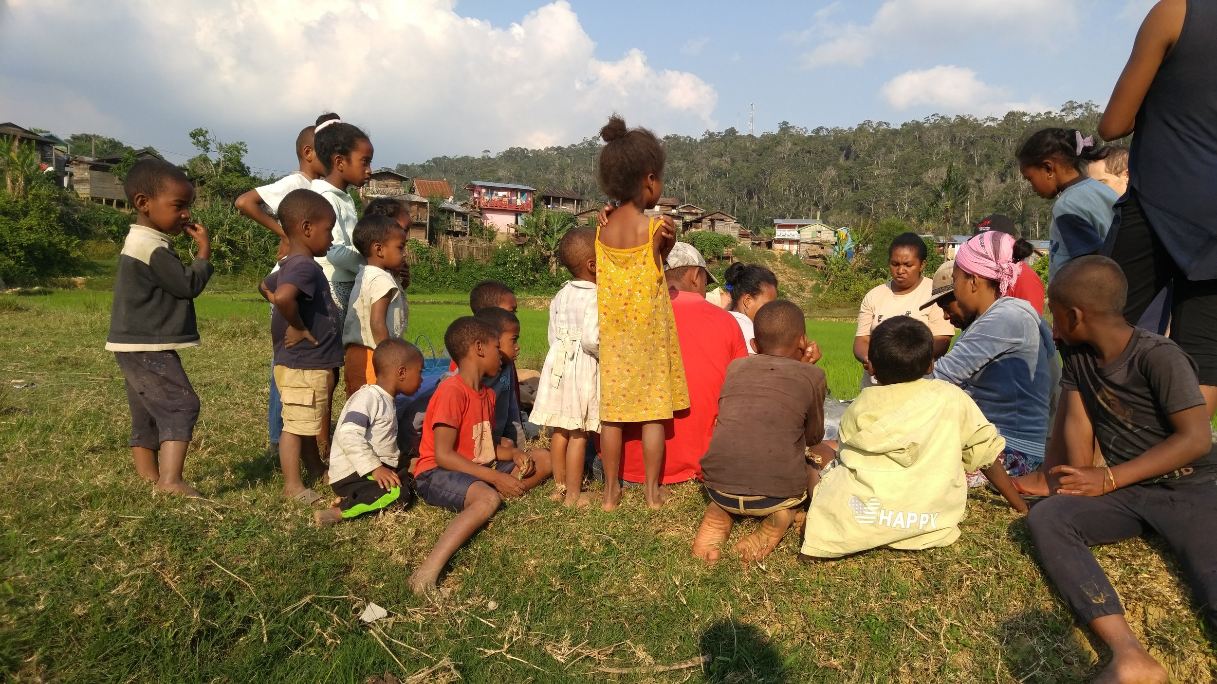 Children from the village observing the amphibian technicians swabbing frogs.