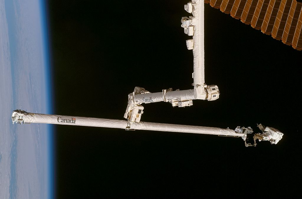 Scott Parazynski on the end of OBSS, being gripped by Canadarm2
