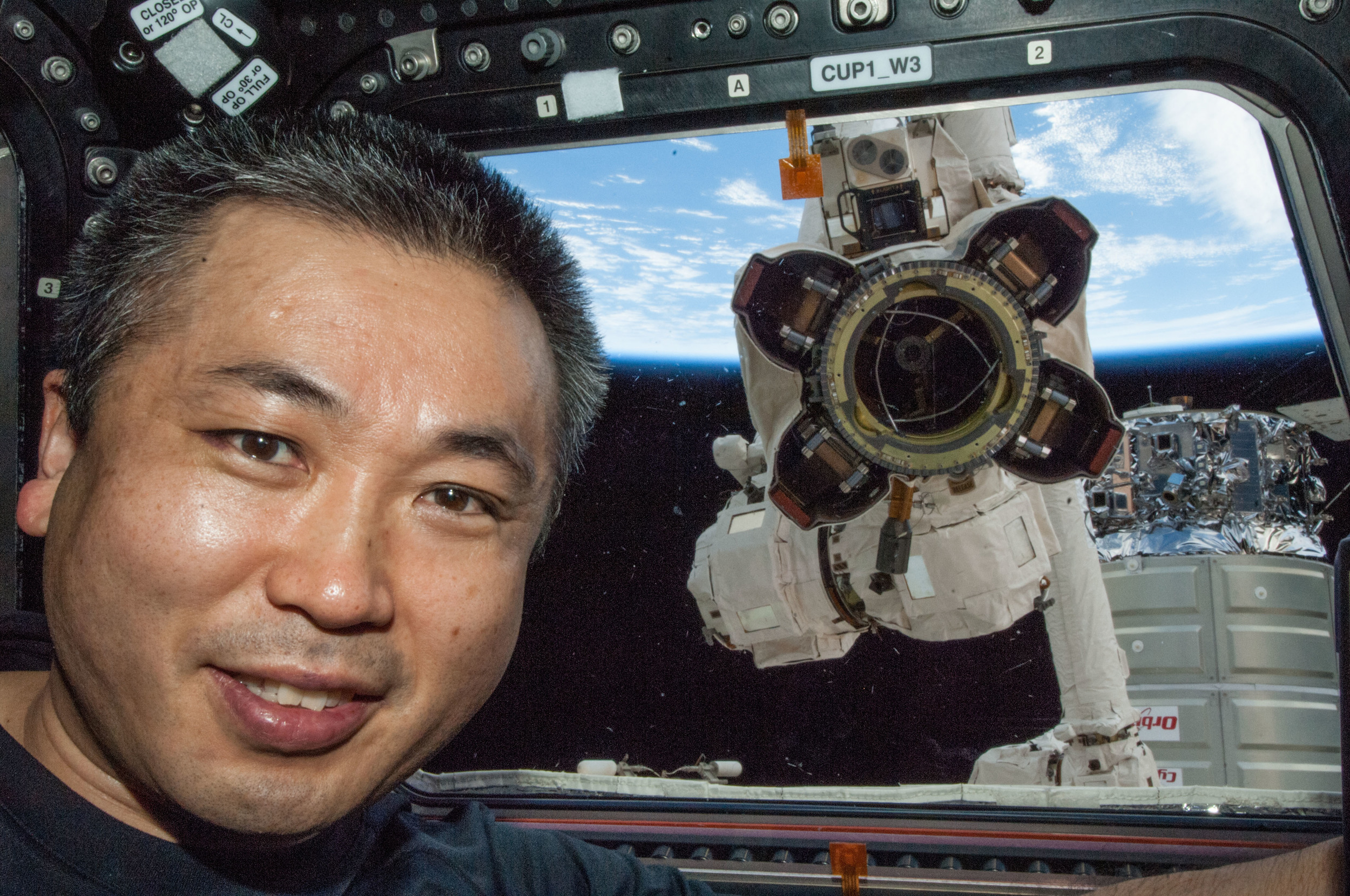 """ISS Commander Koichi Wakata poses with the end effector of Canadarm2. Notice the three semicircle indentationsset in the collar of the inner chamber? Those fit with the """"ramps"""" on a grapple fixture."""