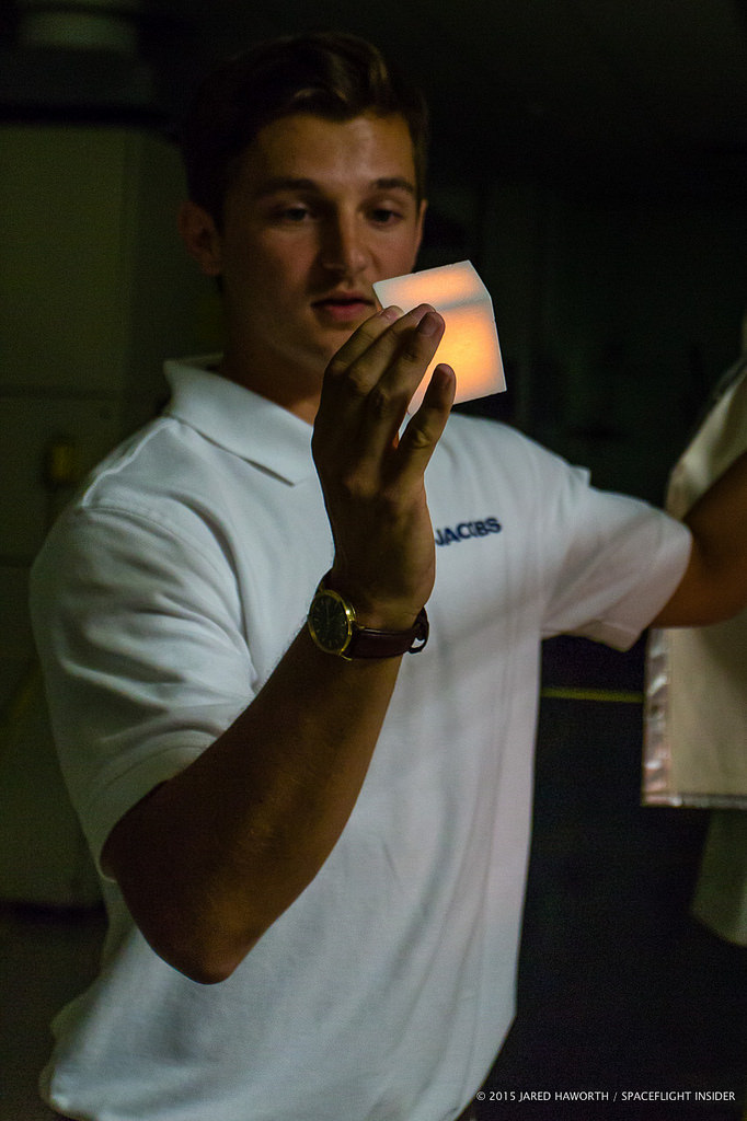 A TPSF employee handles a glowing hot Shuttle tile.