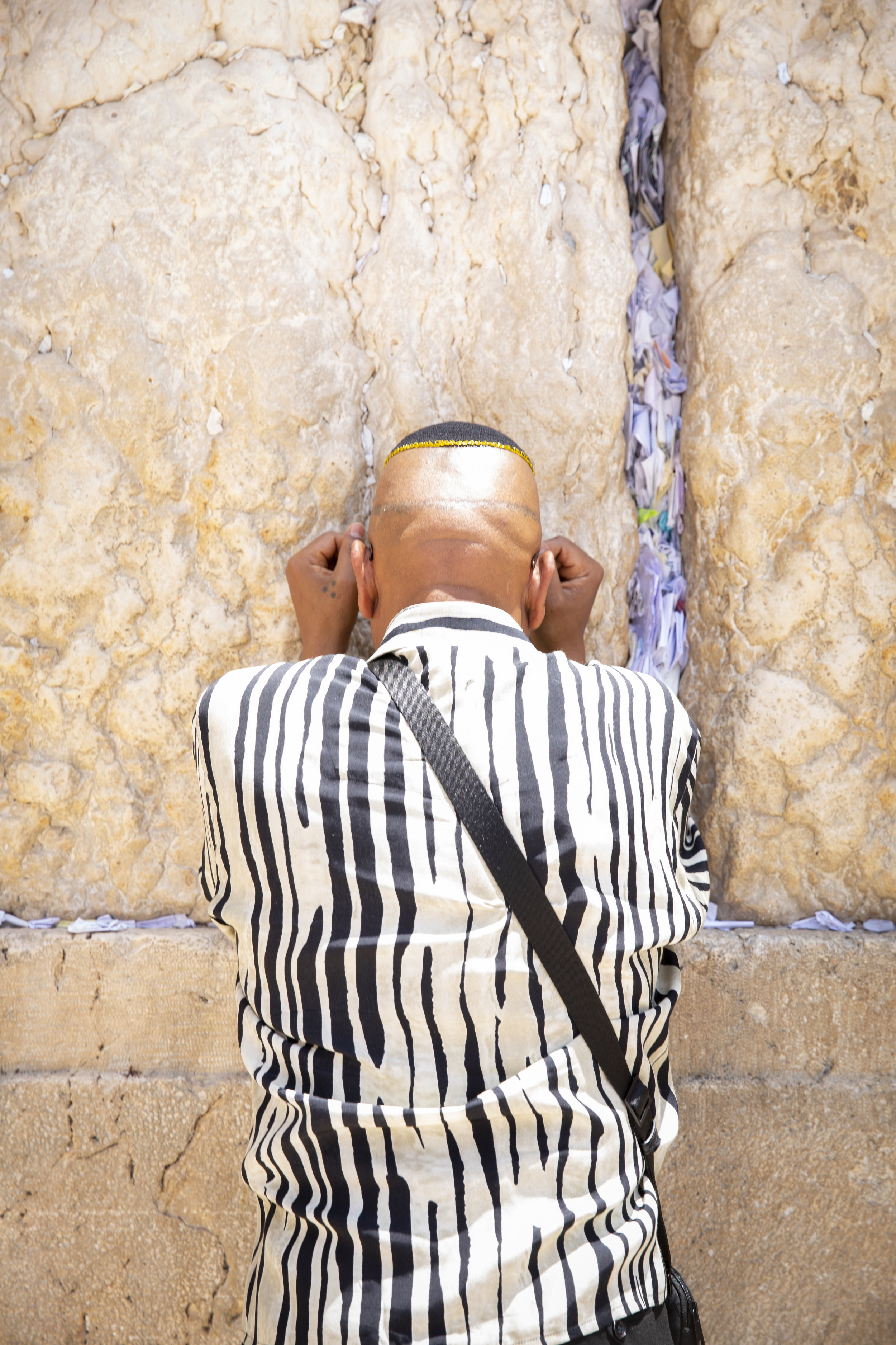 A man leans against the Western Wall in Jerusalem and prays after stuffing a note into the crack of the wall.