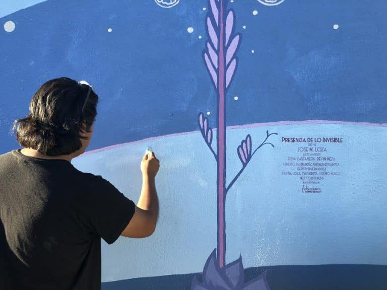 Long Beach artist Jose Loza adds finishing touches to his latest mural, Presencia De Lo Invisible. Photo by Stephanie Rivera.