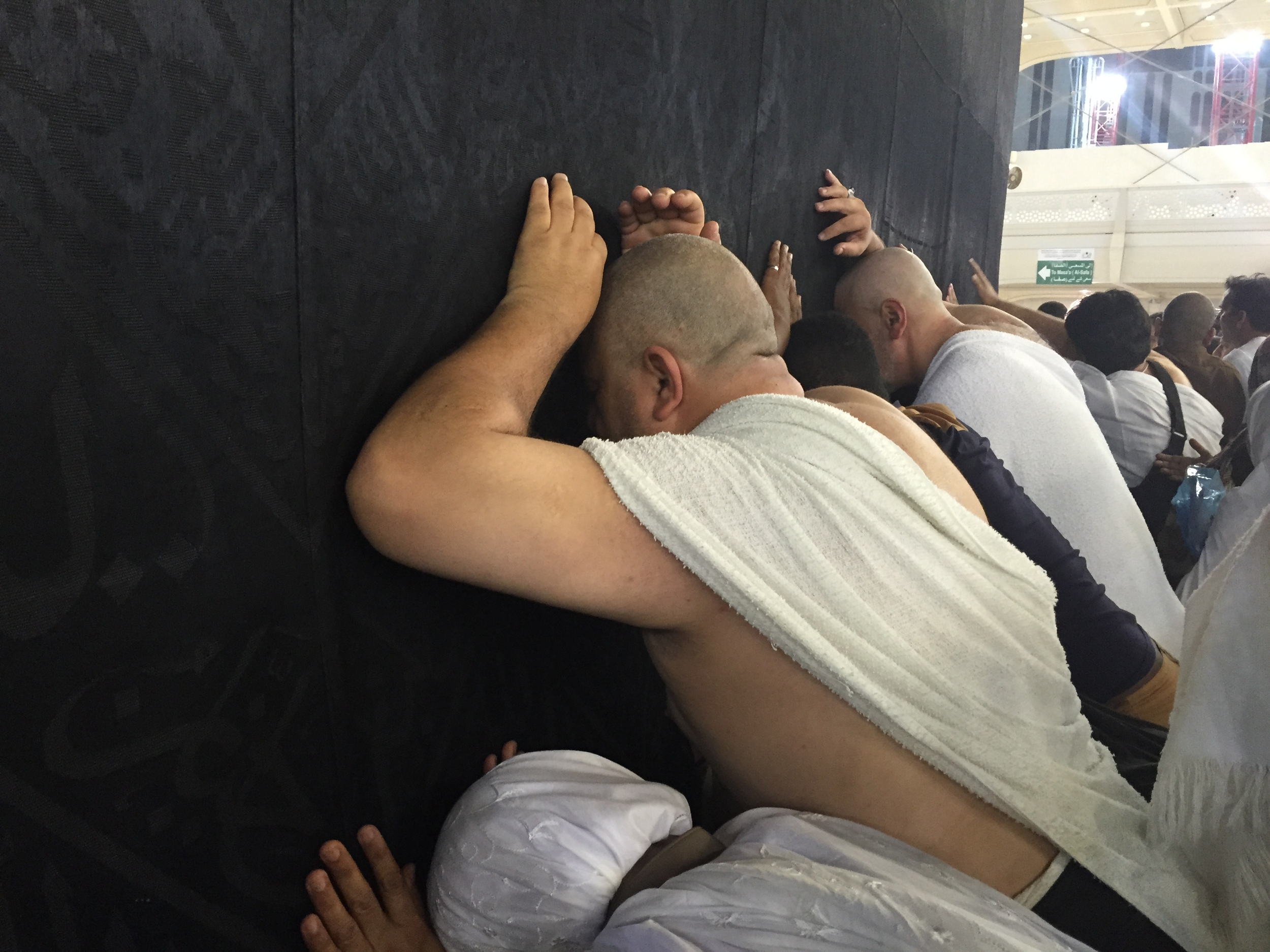 Men and women drape themselves on the Kaaba and pray