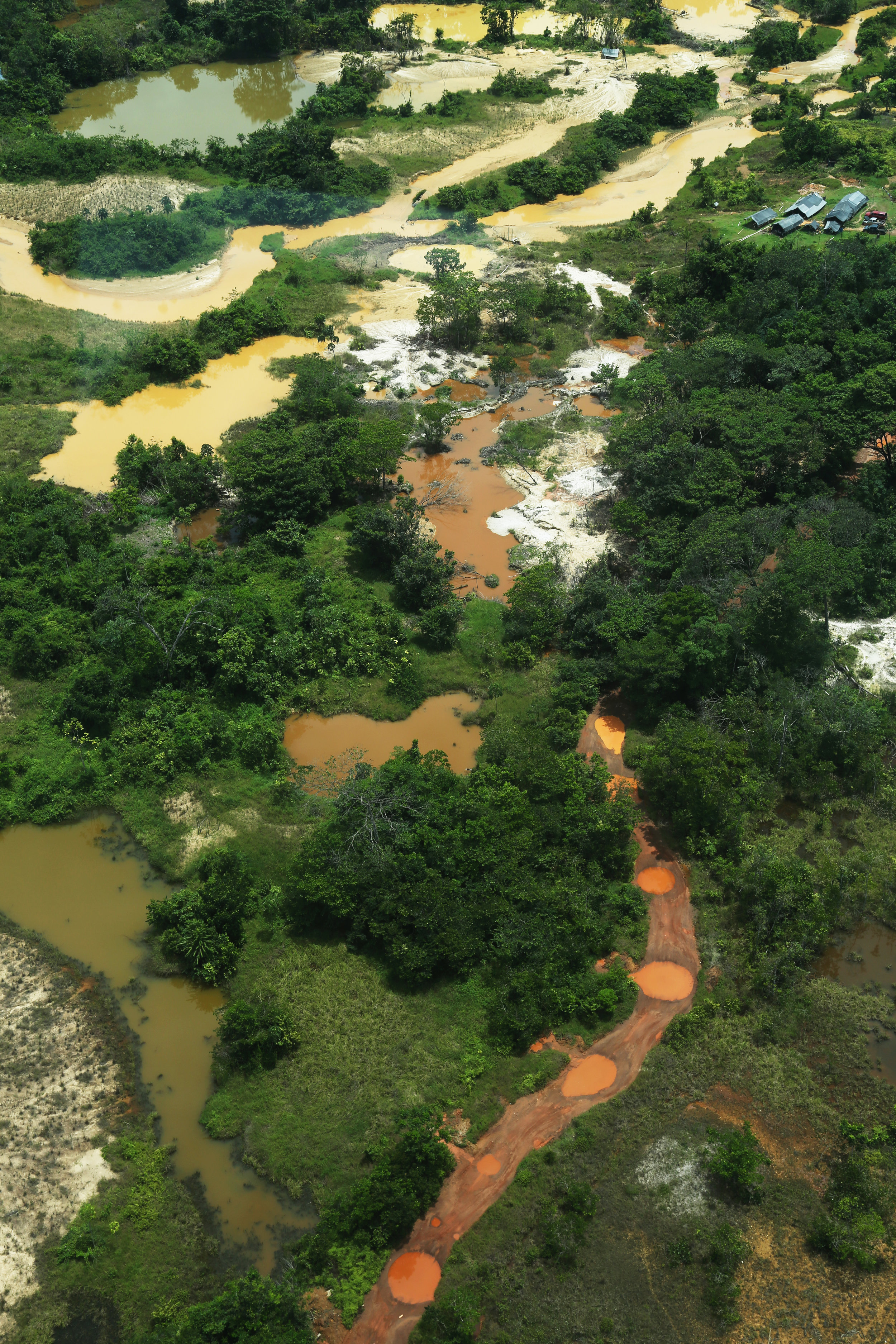 AERIAL OF A GOLD MINING SITE: BECAUSE GUYANA HAS NOT TAPPED INTO THE OIL AND GAS ENERGY SECTOR DUE TO ITS NEIGHBORS BEING VENEZUELA, MINING IS ONE OF THE LARGEST EXTRACTIVE INDUSTRIES WITHIN GUYANA.