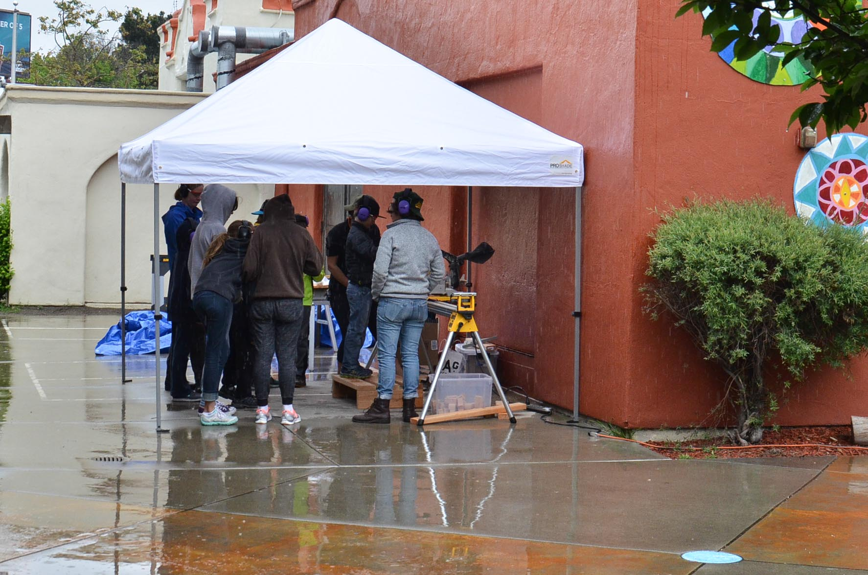The team circles up tight to avoid the rain while learning about making a ready call.