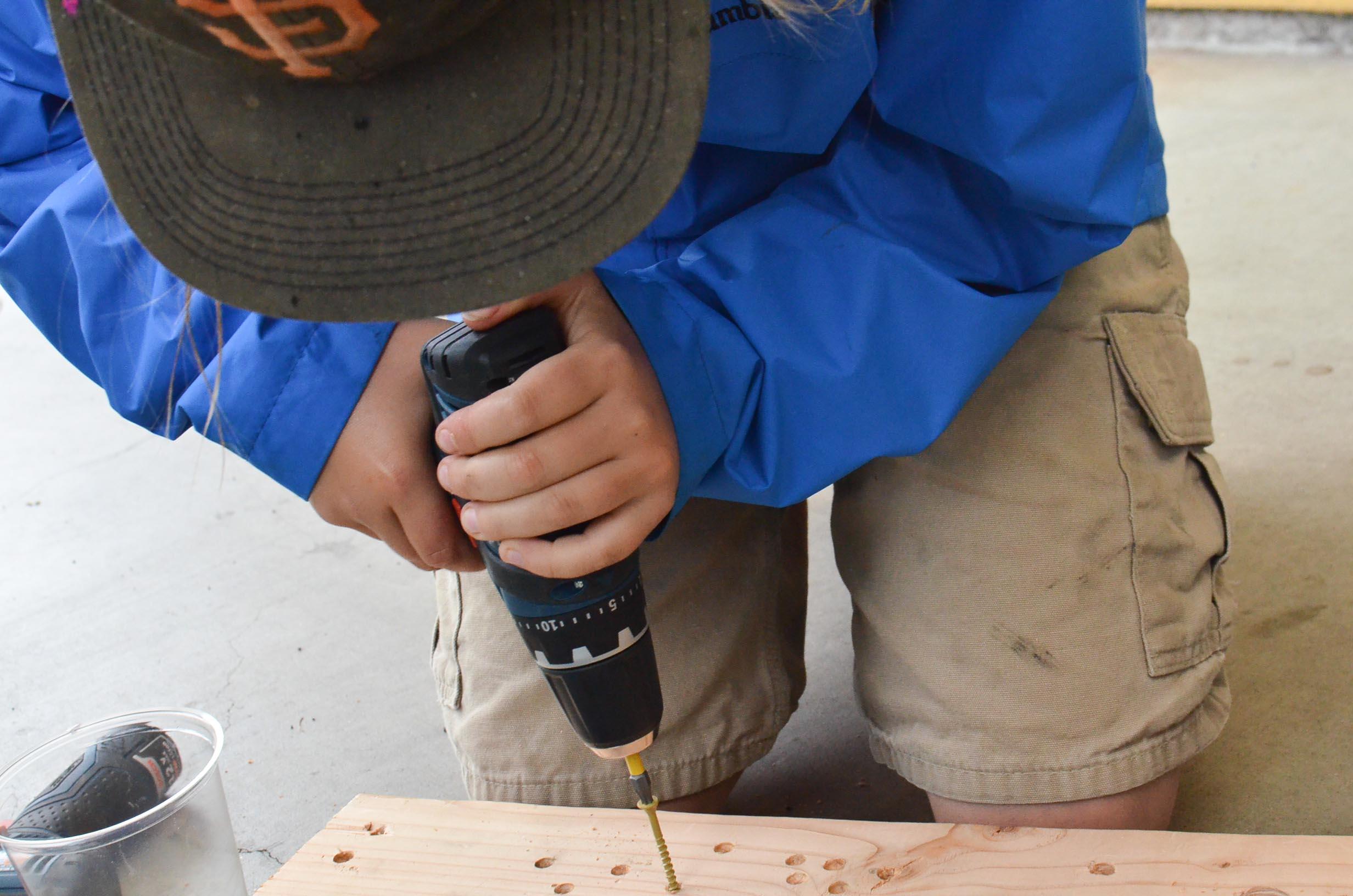 Aiden practices driving lots of screws.
