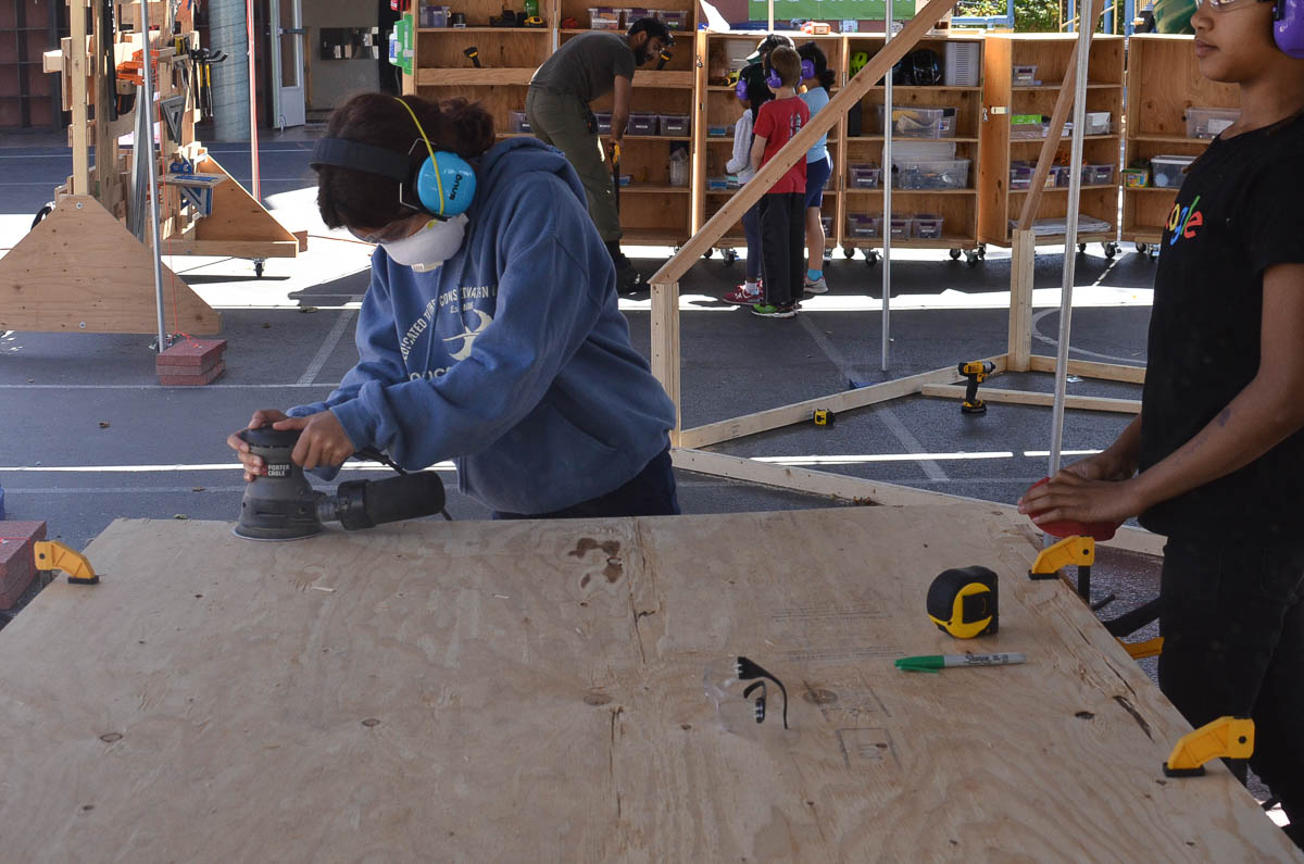 Kaia uses the power sander to smooth a splintery piece of ply.