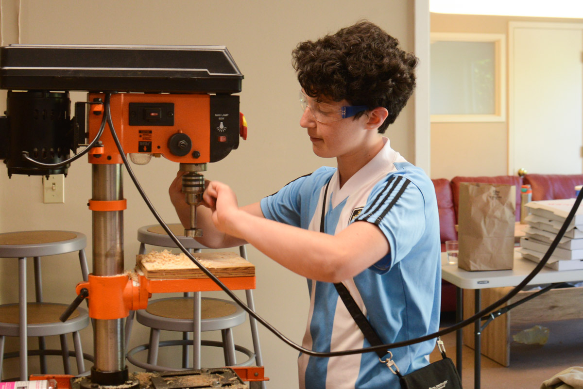 Anabel sets up the drill press to make a perfectly straight hole for their steering device.