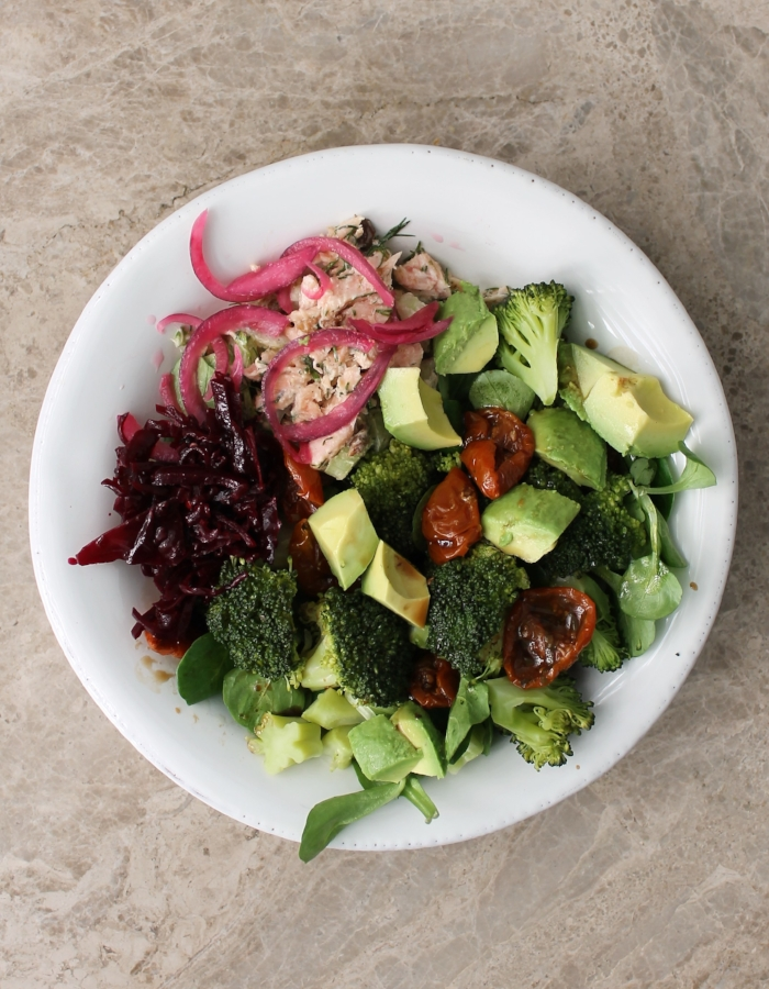 """This  Roasted Salmon & Broccoli Bowl  is one of my favorite meals as of late 🥦⠀ ⠀ Roasted salmon gets a Waldorf-inspired salad makeover. It's flaked and combined with celery, lemon, raisins, dill, and mayo. Top it with quick-pickled onions (because….what doesn't benefit from pickled onions?). Add a generous side of fresh greens, steamed broccoli, avocado, sundried tomatoes, and sauerkraut. Drizzle with a bit of balsamic, and you've got the happiest of happy meals 🍋🌱🍅🥑⠀  Vegans, instead of salmon, make the Chickpea """"Tuna"""" Salad on the blog 👈🏼👀🙅🏻♀️🐟"""