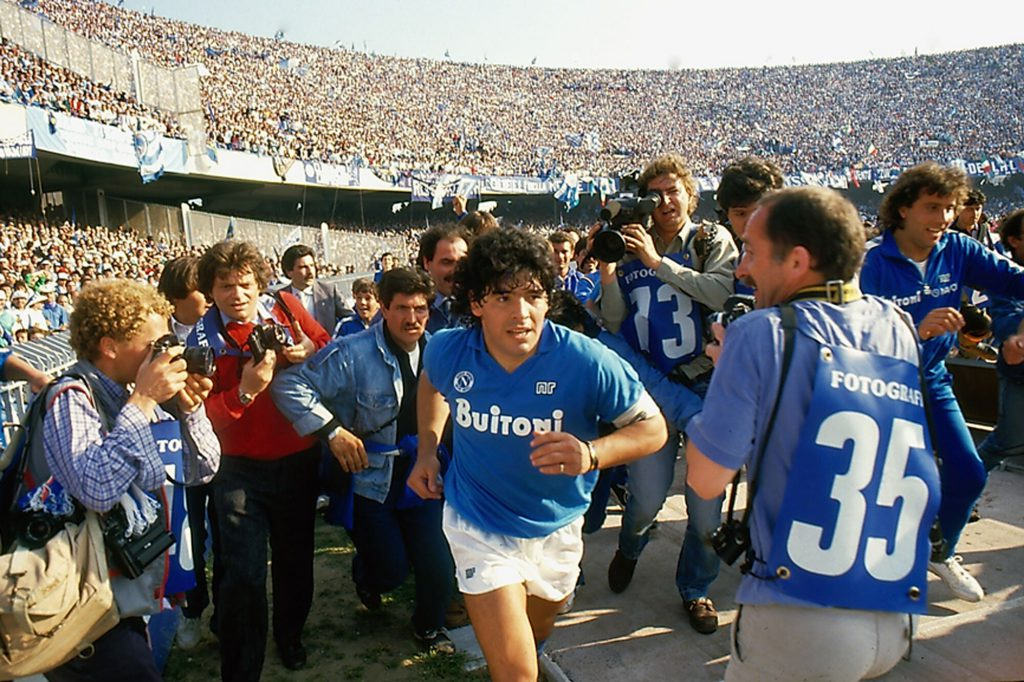 Footage of a young Diego Maradona as he enters the pitch swarmed by photographers and cameramen as seen in  Diego Maradona .