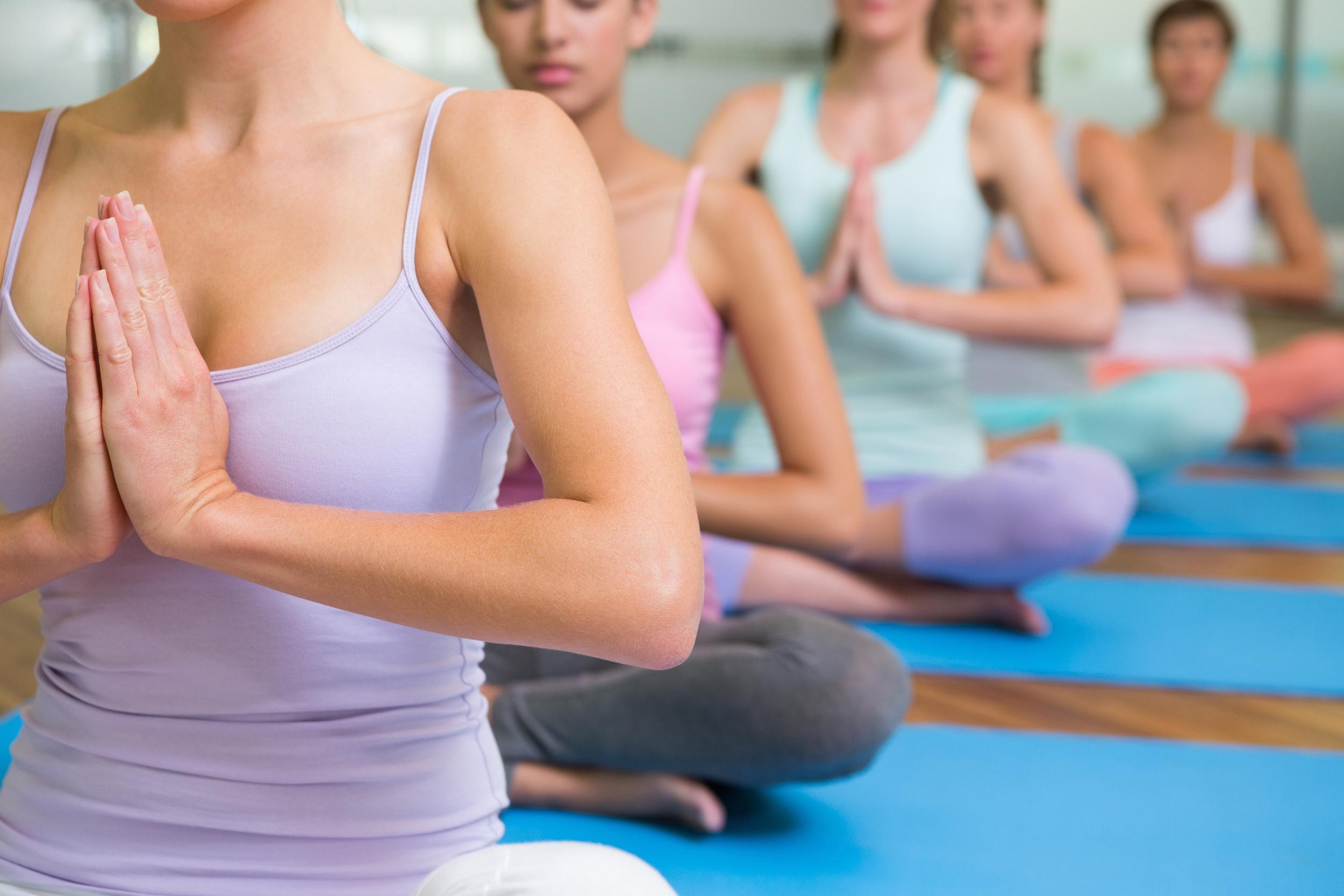 bigstock-Yoga-class-in-lotus-pose-in-fi-68712805.jpg