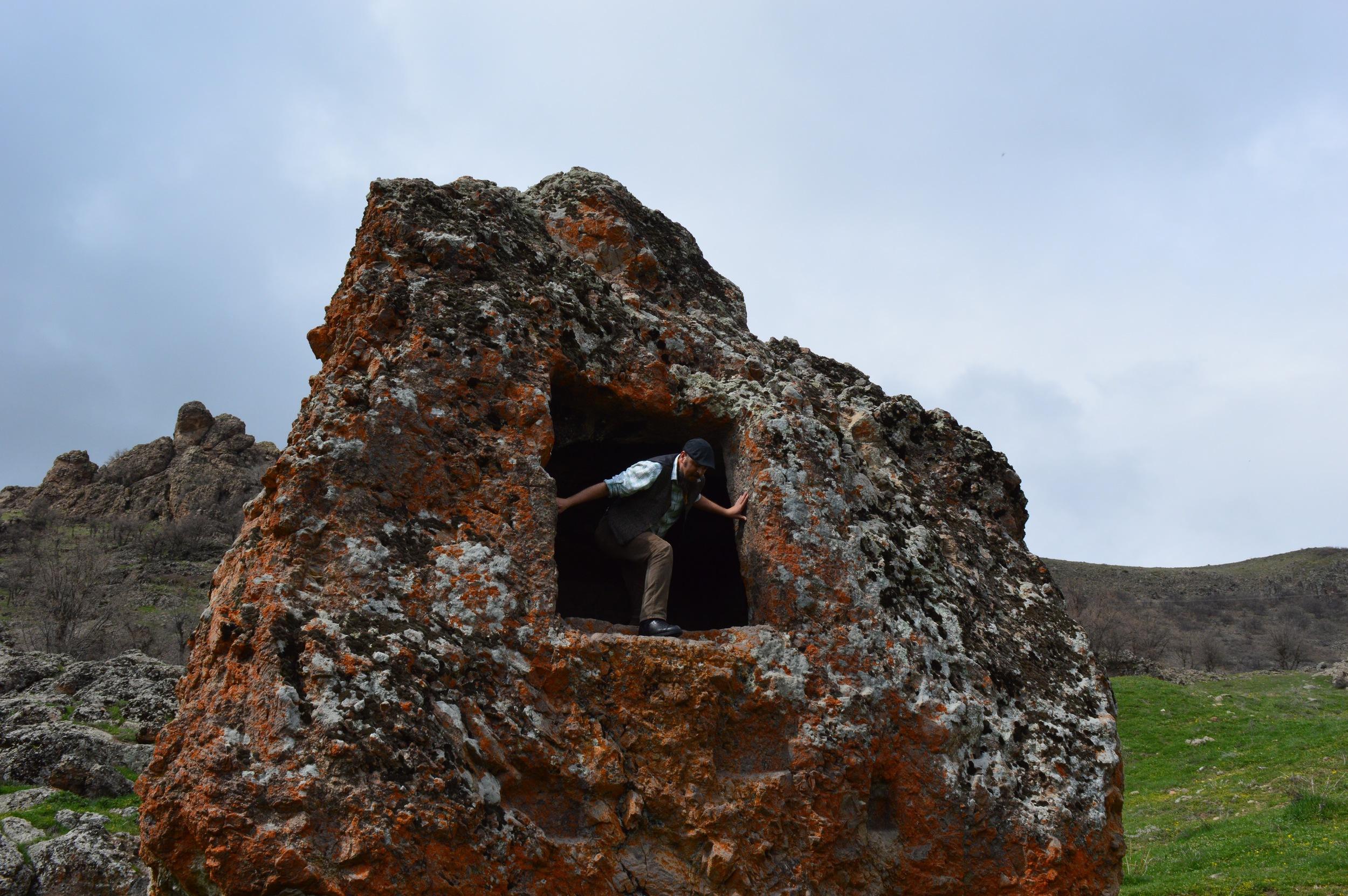 Serkan climbing into the rock-temple.