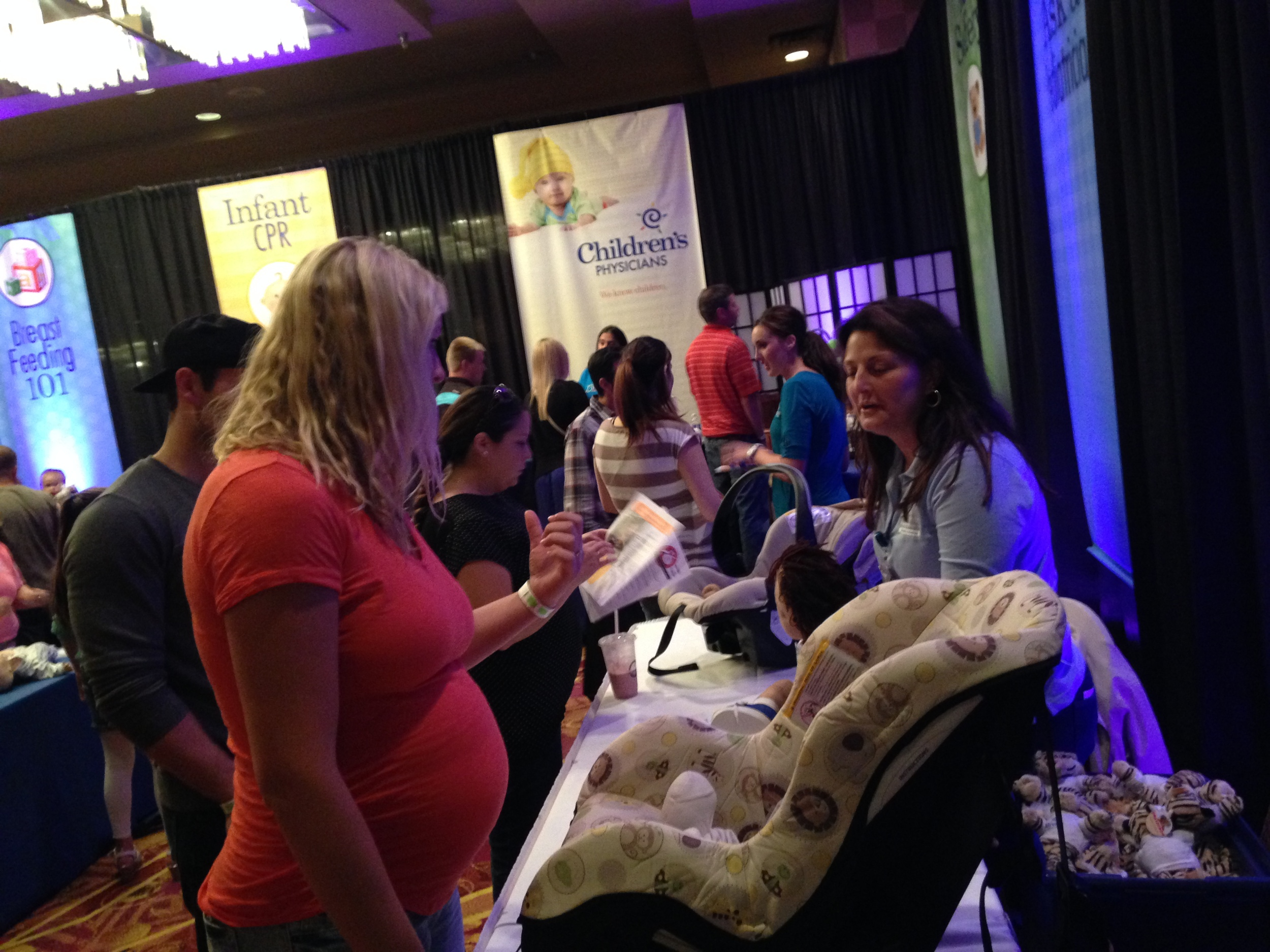 """Baby Safety Sanctuary where families learn car seat safety, infant CPR, and how to set up a safe nursery!     """"I am sitting in line witnessing great conversations between first time expecting moms, a mom with her expecting daughter, strangers who have a baby bump in common.    It's a beautiful thing!    - Johanna F's Facebook message while waiting in line of 1000 for Swag Bags      """"I give a five star for the event. This was our first time going. I was skeptical because of the reviews from last year but obviously they listened to the peoples comments. Everyone was so nice and helpful. I loved all the vendors. I also loved the fact that there were actual gifts and free samples. It seems like these days its really hard to find samples and in order to try something out you have to buy it. There was a mommy station and classes too. Lots of good information, and good people.    I will come again and tell my mommy friends about it too. Thank you so much for setting up such a wonderful event!""""    - Sara K's Facebook Review of June 2016 Show      """"My daughter and I had a great time. This was a first for both of us, and there was so much to see and learn.. And to top it off she won Most deserving mother to be....so exciting...."""" - Tracie B Grandma and attendee posting her experience on Facebook"""