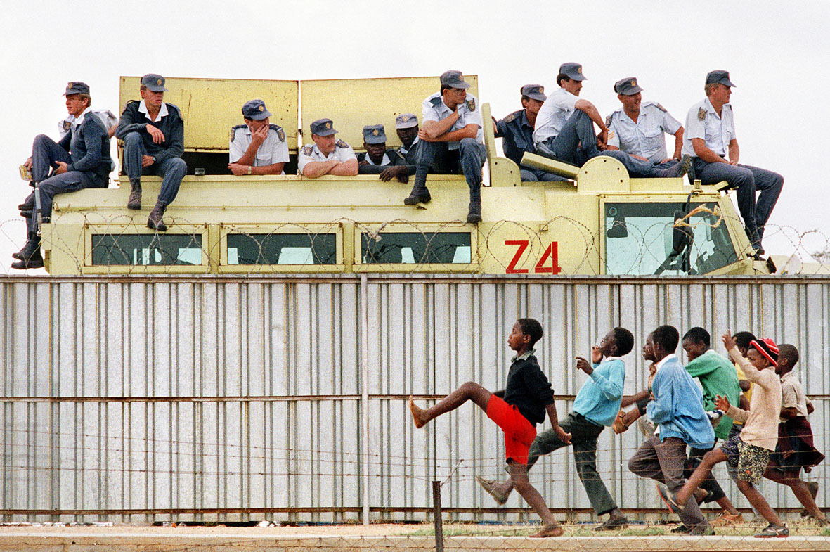 Police watch an ANC rally while children taunt them by toyi-toying on the other side of the fence. Johannesburg. 1991. (Photo credit Graeme Williams, in his series  The Struggle for Democracy – 1989 to 1994 )
