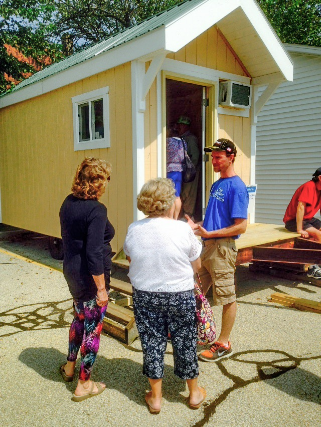 Redeemer Lutheran Church Tiny House volunteer chats outside the prototype home.