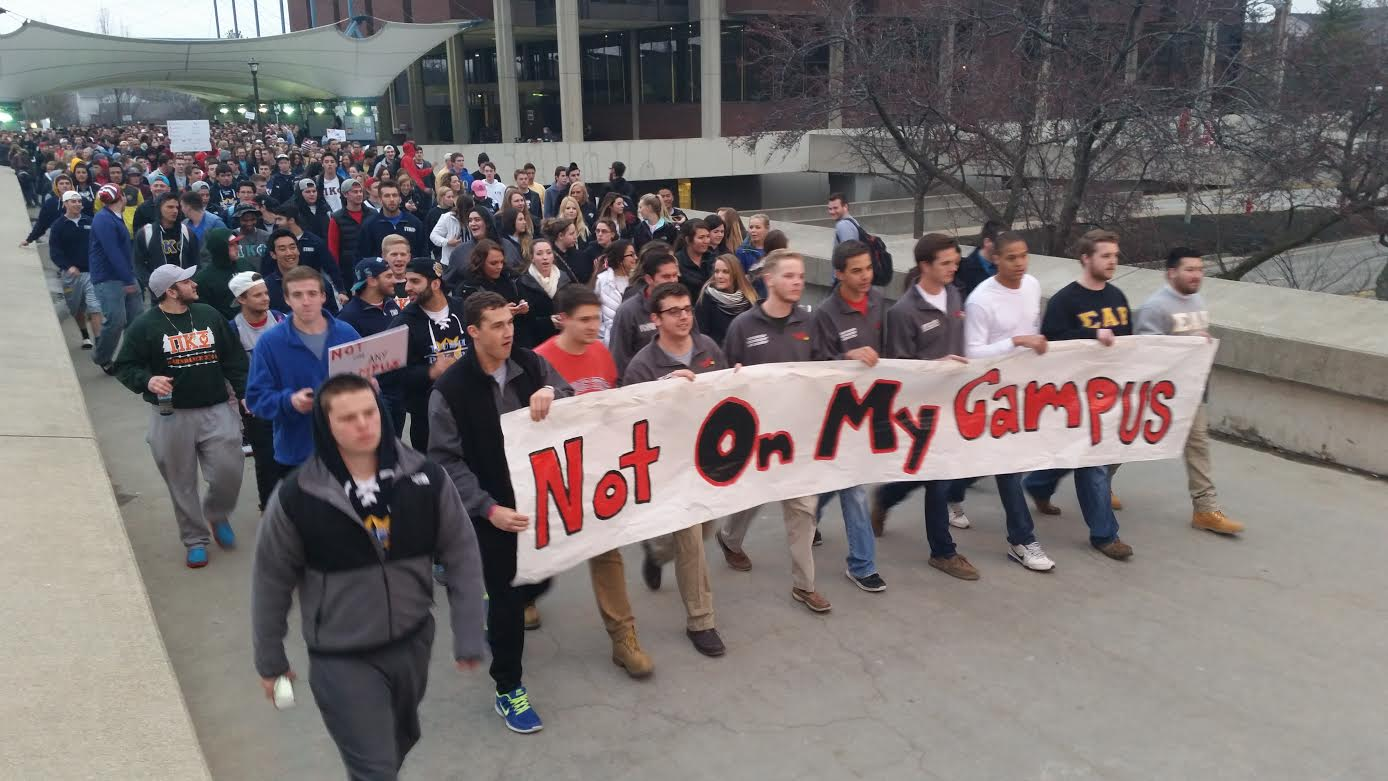 Concerns about racism and inappropriate conduct among fraternities at the national level, as well as alarm over racist student-originated social media posts following recent police protests led Illinois State University administrators and students in spring 2015 to take a hard look at attitudes and diversity. Here, ISU Greek organizations march across campus with a message echoing NIOT:B/N's.