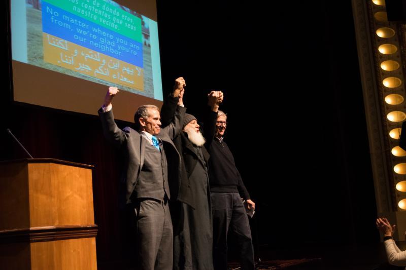 Bloomington Mayor Tari Renner joining hands with Bloomington's Imam Abu-Emad Al-Talla and Mayor Chris Koos of Normal. (Photo by Cristian Jaramillo/WGLT)