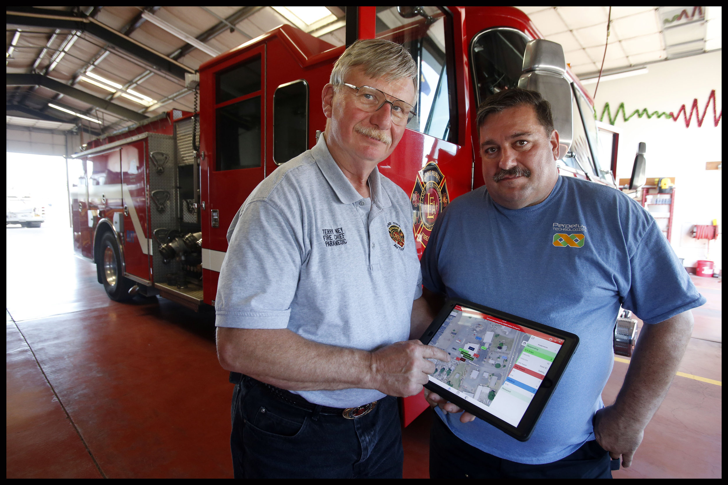 1/2 – Mike Speiser, right, a volunteer firefighter and software developer, worked with local fire chiefs, including Terry Ney at Lane County Fire, to develop software to improve emergency response to fires, wrecks, and other emergencies. This homegrown technology is being sold nationally from their offices in Eugene. (Andy Nelson/The Register-Guard)