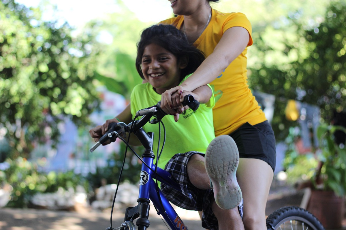 Karen riding her bike with Daniella, a full time employee of the Children of Love Foundation (photo by Mallory Lehenbauer).