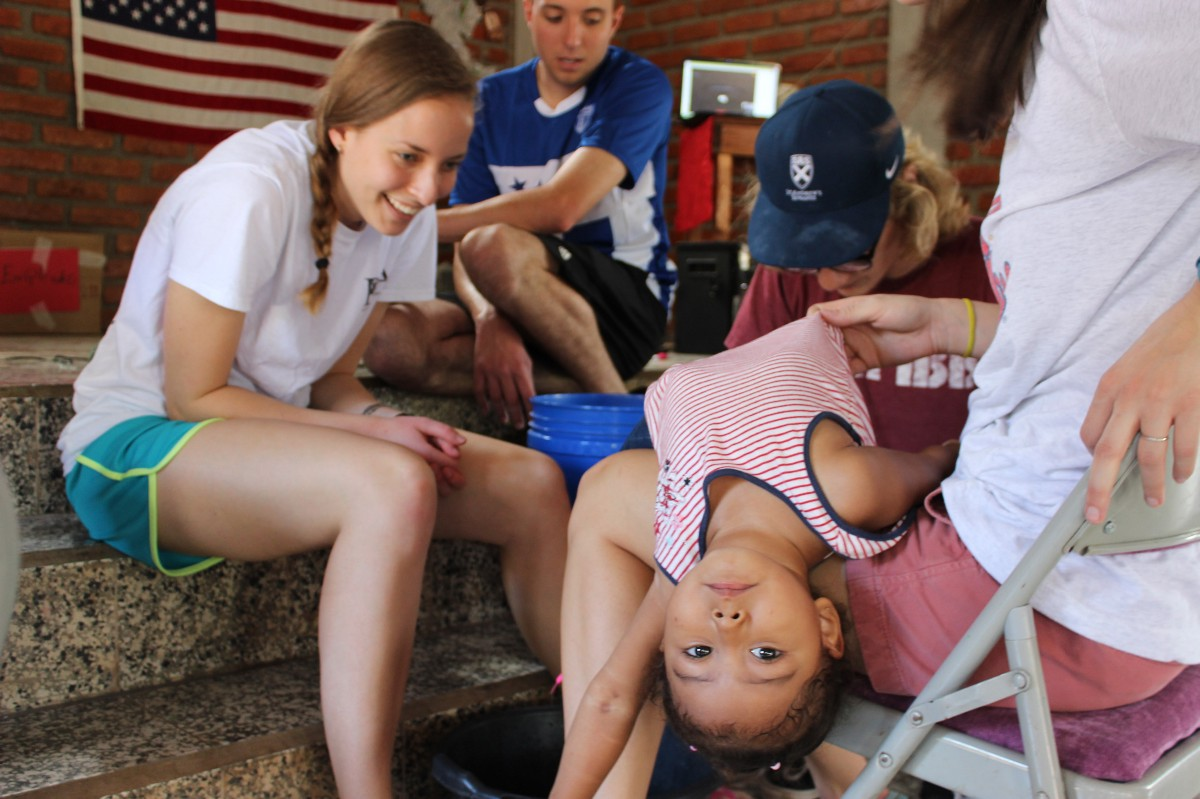 Natalie Duda washes the feet and puts shoes on a child from the community.