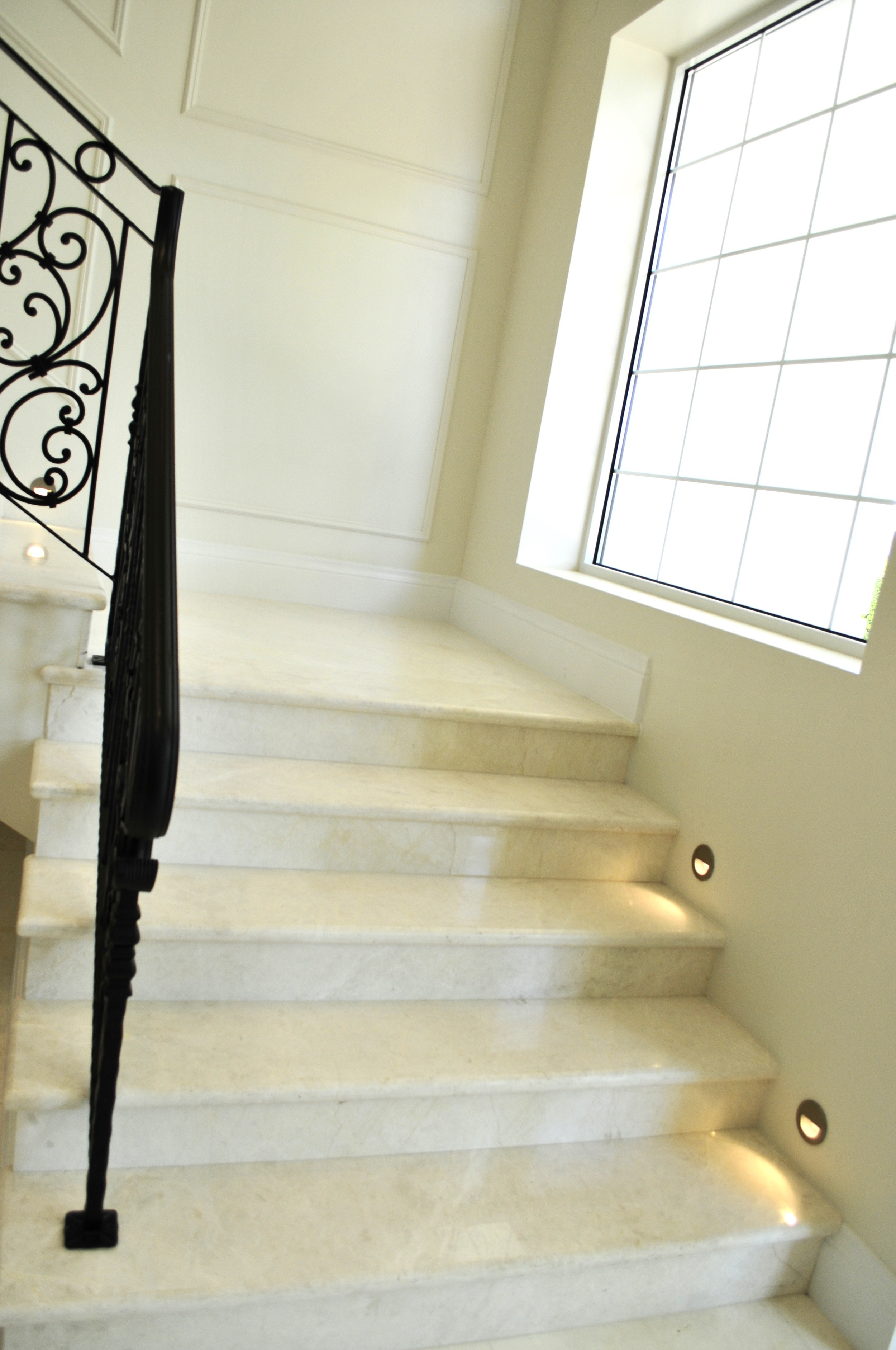 Custom made wrought iron railings made by Artisan Metal works, Marble slab trees and risers, flush mounted low voltage stair lights.jpg