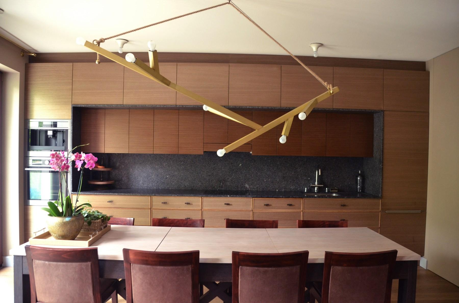 Kuchnia na jednej ścianie stanowi tło salonu