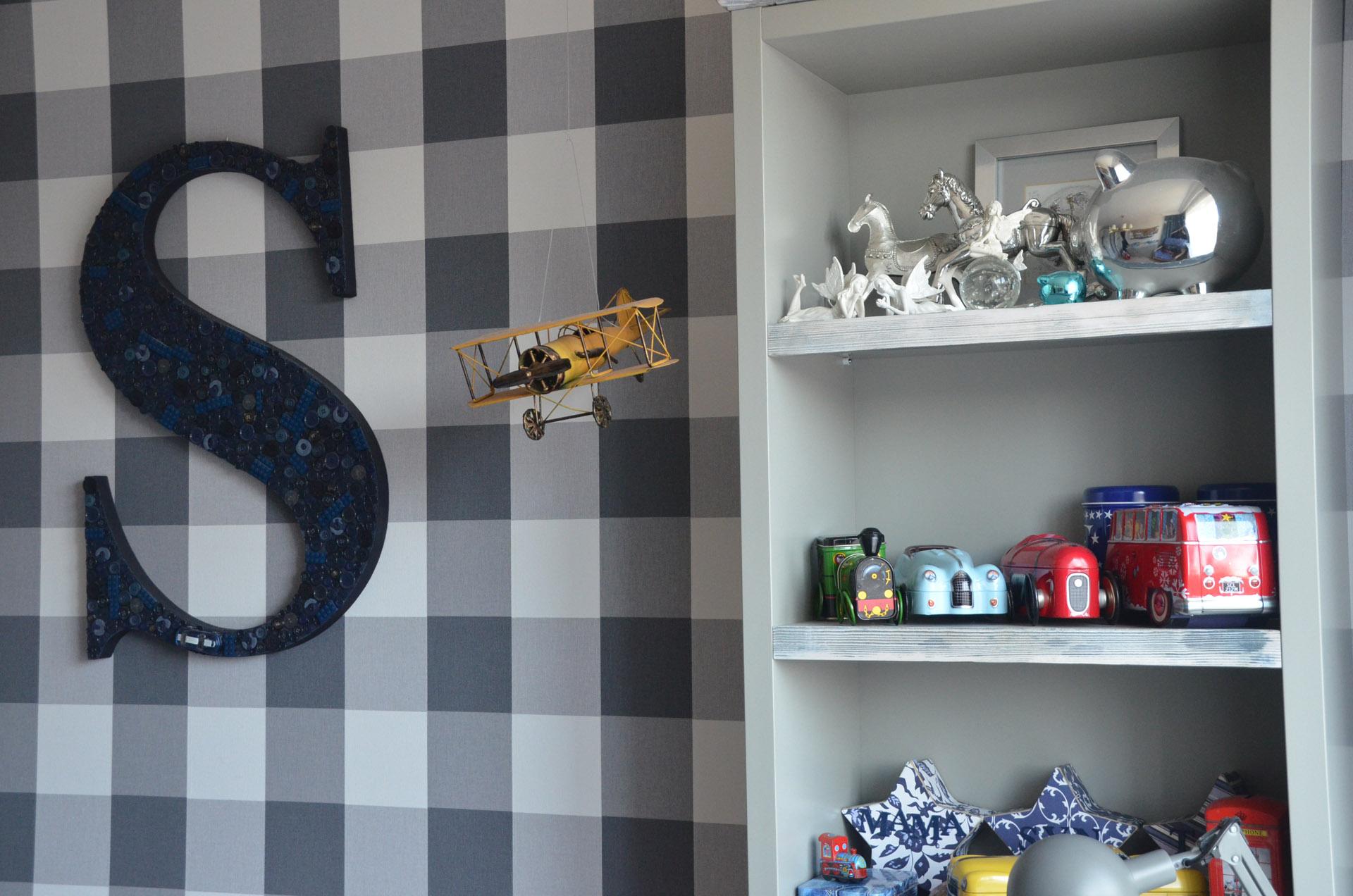 Mocna tapeta stanowi tło dla szarych mebli w dziecięcym pokoju