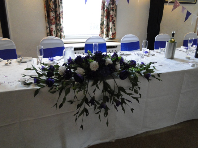 Top Table Display - Large Display Hanging Over Front With Cadbury Purple & Ivory Roses, Purple & Ivory Lisianthus