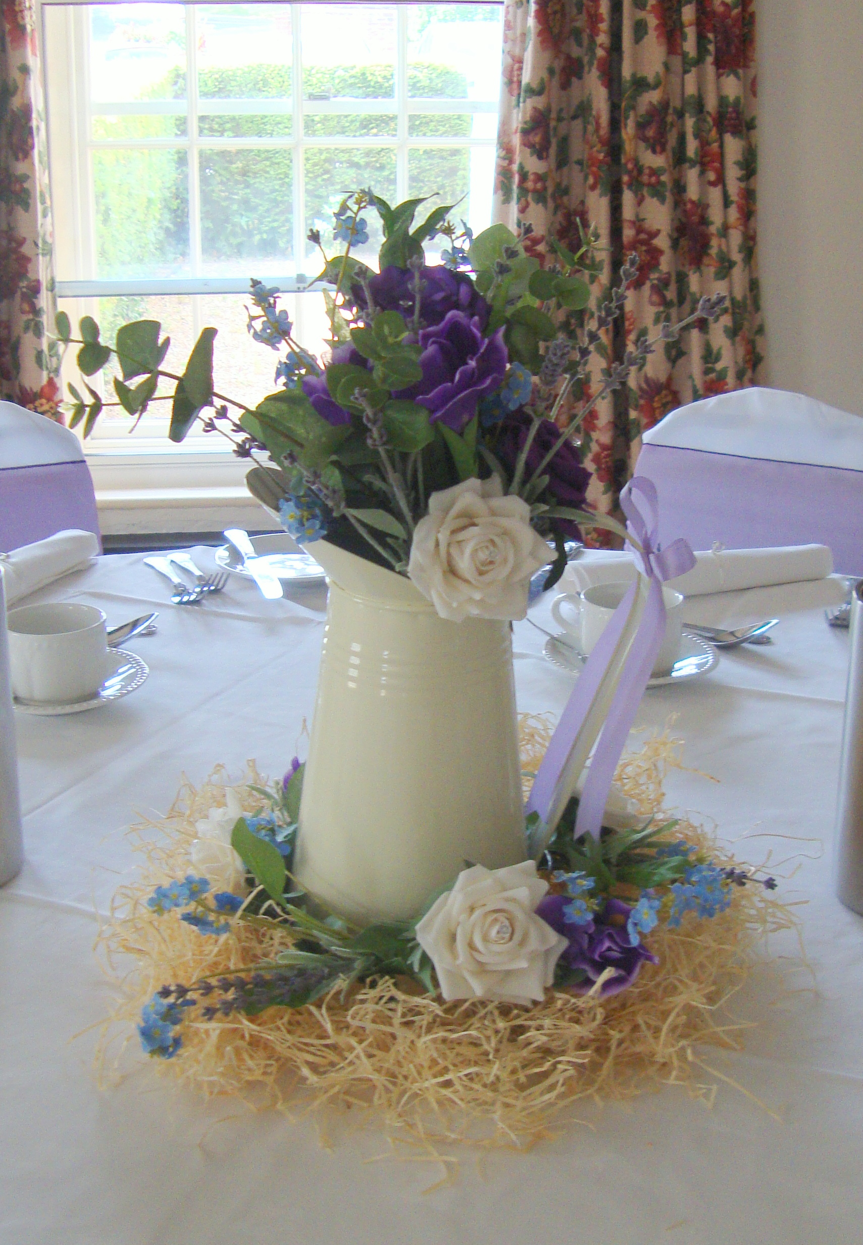Guest Table Arrangement - Jug Display Sitting on Straw, With Purple & Ivory Roses, Purple Iris, Eucalyptus With Matching Garland
