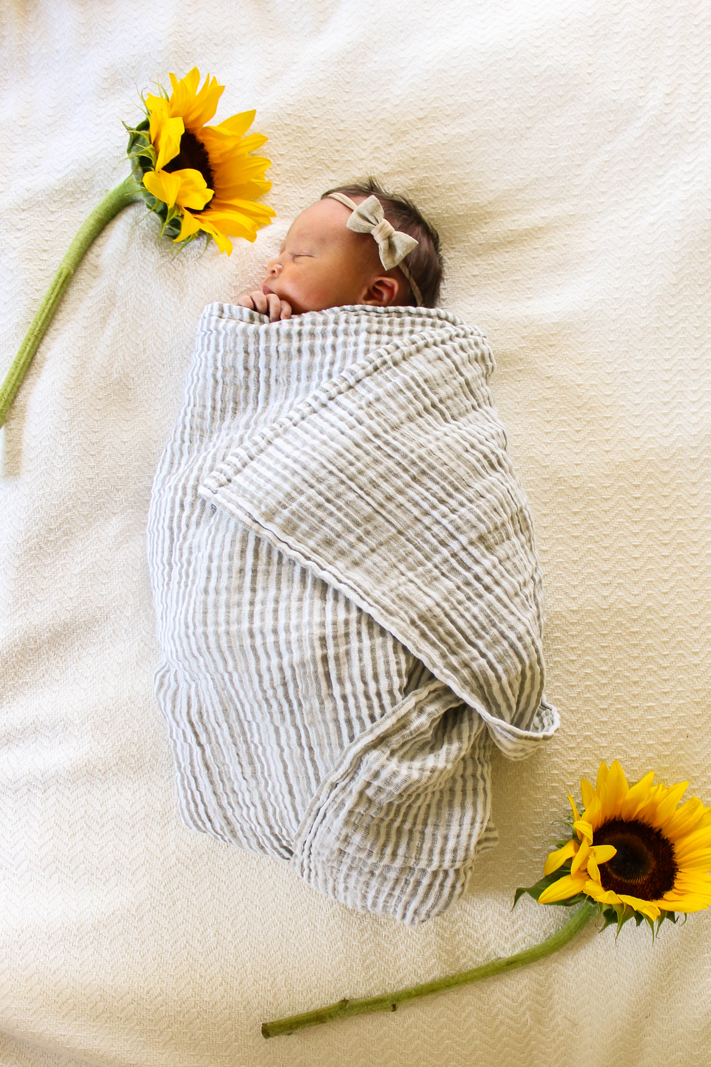 newborn photo with sunflowers, little unicorn striped swaddle