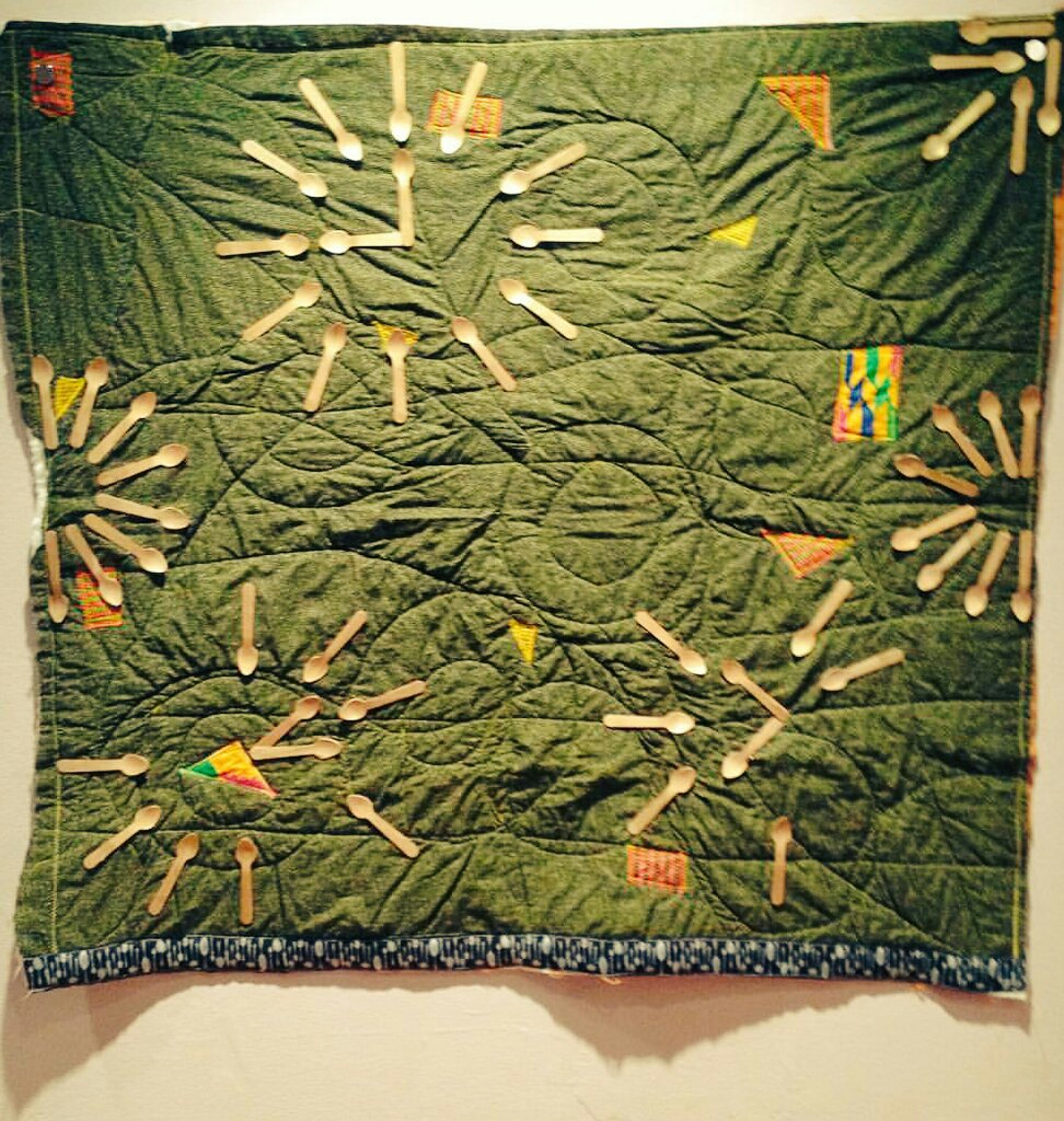 [Image: a quilt hangs on a gallery wall. The quilt has a dark green w yellow dots fabric background. There are scattered patches of #kente style cloth cut in squares, rectangles, and triangles appliquéd on top of the green background. There are three clocks made of small wooden spoons painted gold. The first, top-center-left, contains all 12 hours and is set to 9 o'clock. The 2nd, bottom left is set to 1:14 and is missing the hours 3, 5, 10, 11. The third, bottom right, is set to 10:38 and is missing the hours 11, 12, 3, 4, 5, 8. In the center of the left and right edges, half circles of gold spoons fan out toward the middle. In the upper right corner, 5 spoons are placed in a tight diamond formation, some point towards the center and some point away. Along the bottom, a brown ribbon with images of silver spoons in various sizes. The piece is quilted with long diagonal lines and intersecting circles.]