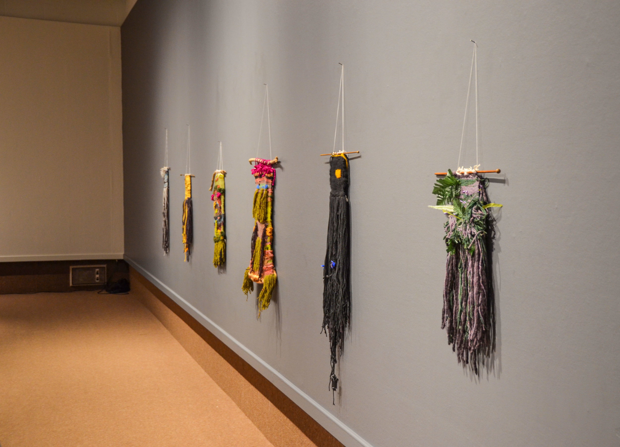 L - R: Audre Lorde, June Jordan, Self Portrait #1 (present), Self Portrait #2 (as ancestor) Jean-Michel Basquiat, Octavia Butler.   Image Description: six woven tapestries hang on a dark grey wall above a sable coloured carpet.