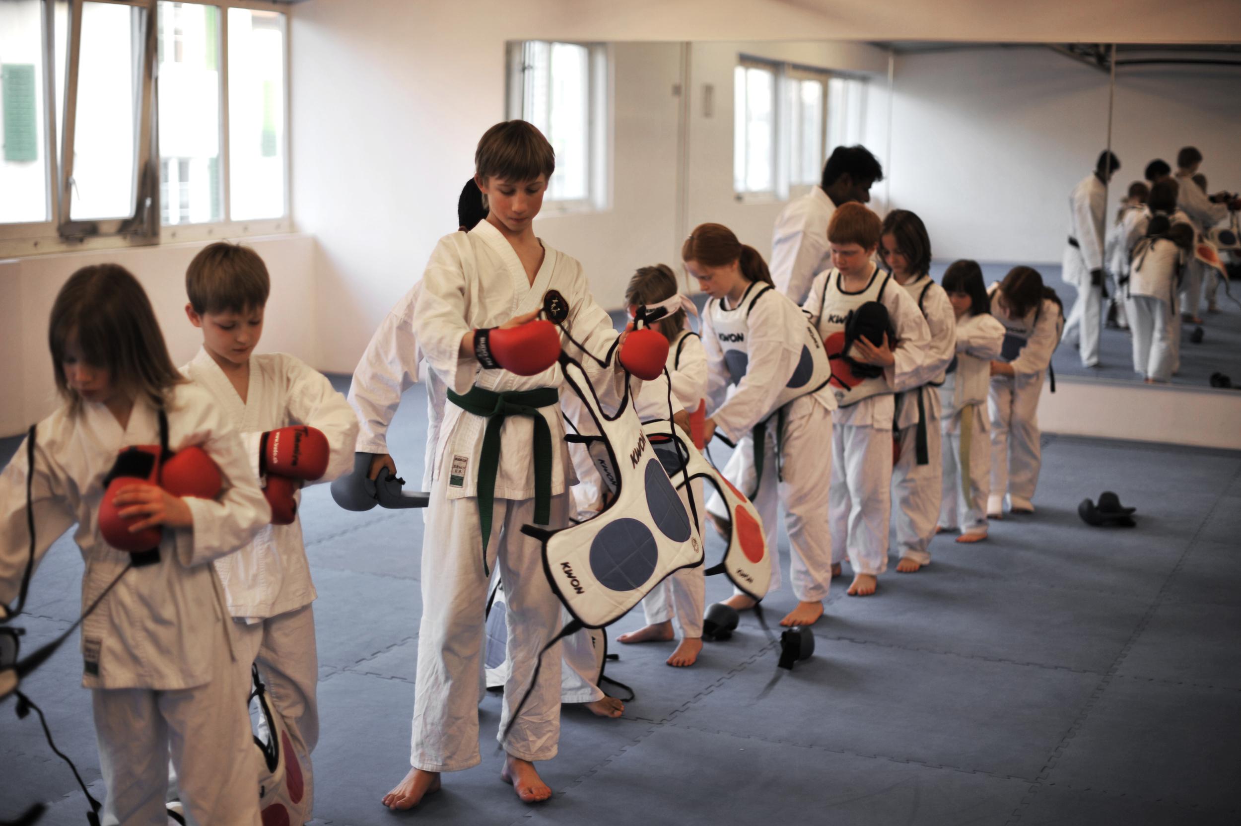 Im Dojo entstehen oft enge Freundschaften, Kinder helfen sich gegenseitig beim Anziehen der Schutzausrüstung.