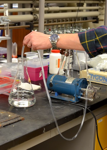 Pumping water samples through a filter for solid state extraction.
