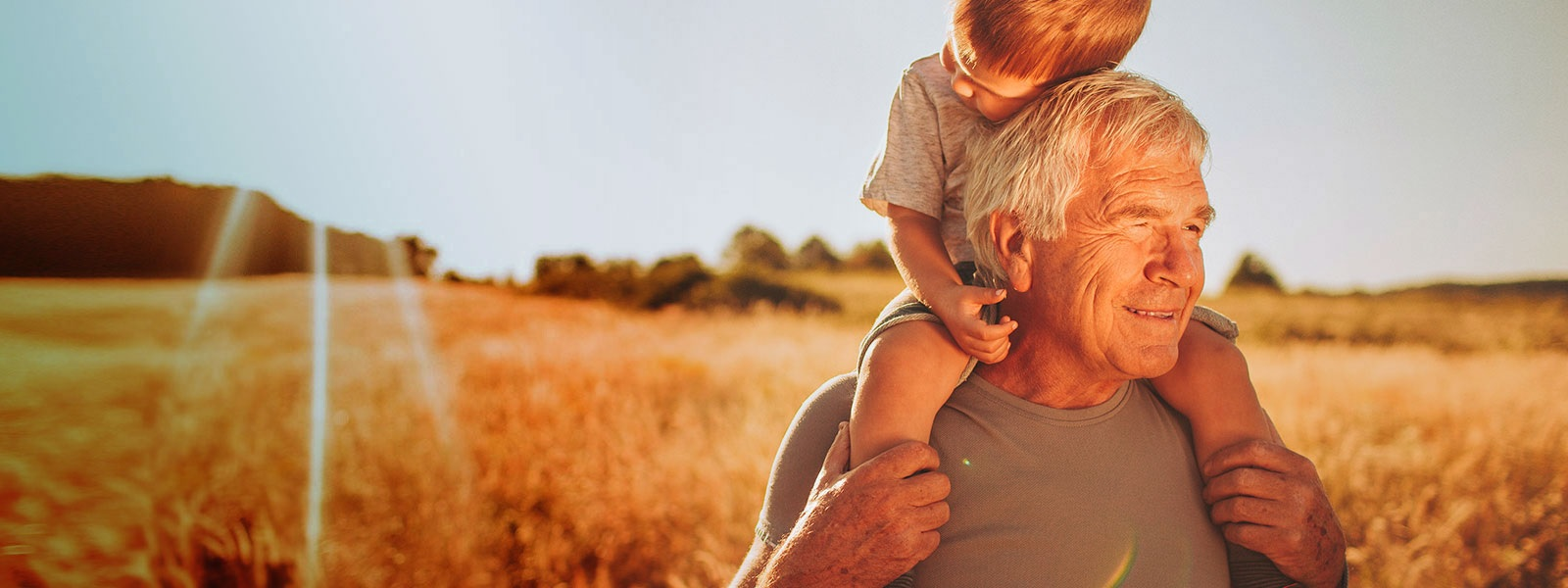 grandpa and grandson in wheat field with sunset behind them.jpg